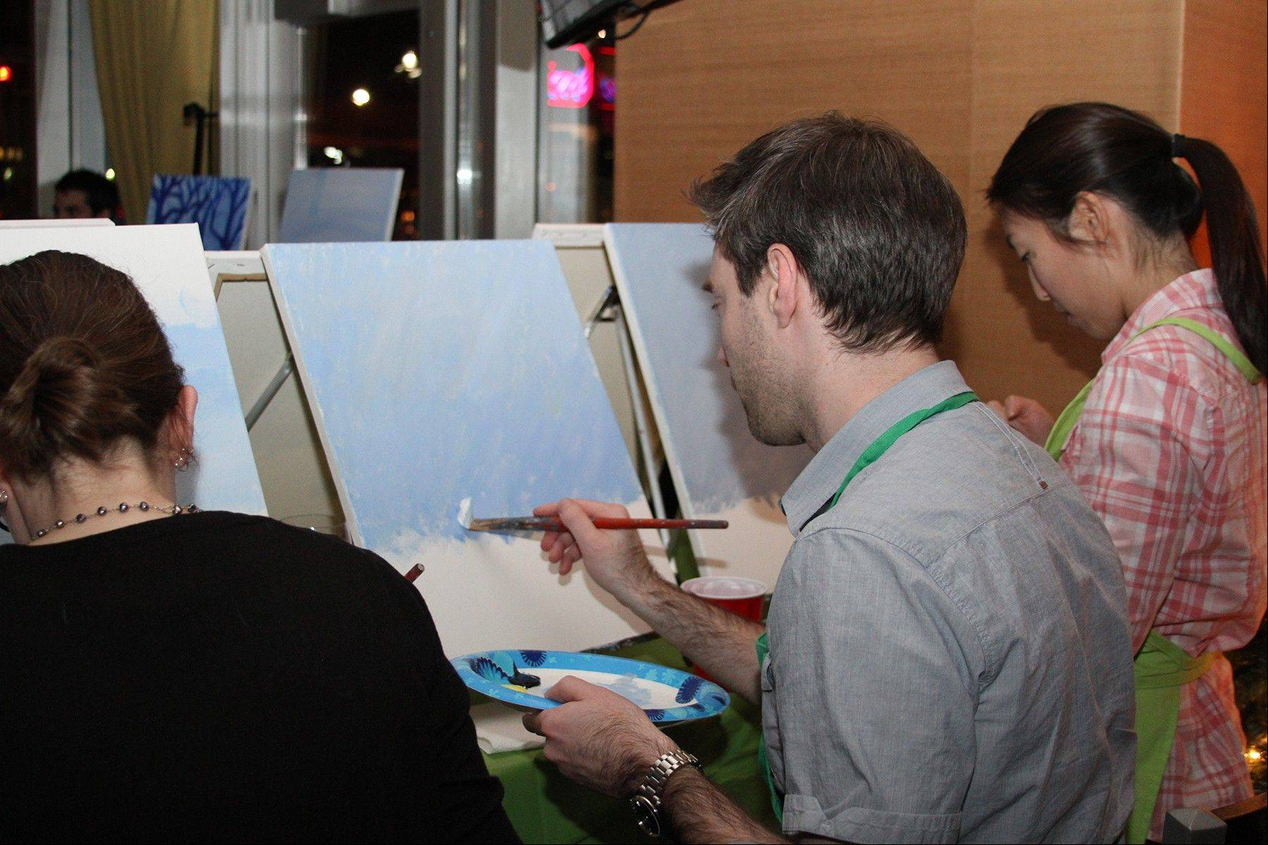 In this Dec. 4, 2013, photo, provided by Lattice Engines, Lattice Engines�s Boston office participates in Paint Nite, in Boston. Paint Nite is a service event that gives painting lessons at bars and restaurants. About sixty-five people attended.