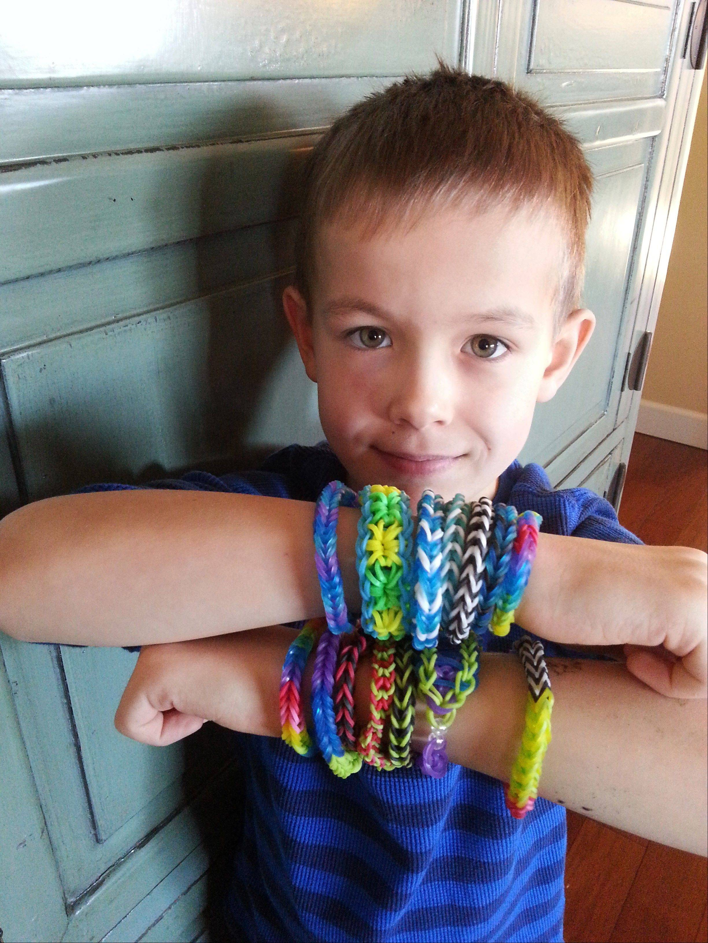 Cooper Volkman, 8, wears loom band bracelets that he made. The current craze for kids, Rainbow Loom bands and their many knockoffs, is surprising parents and child development experts.