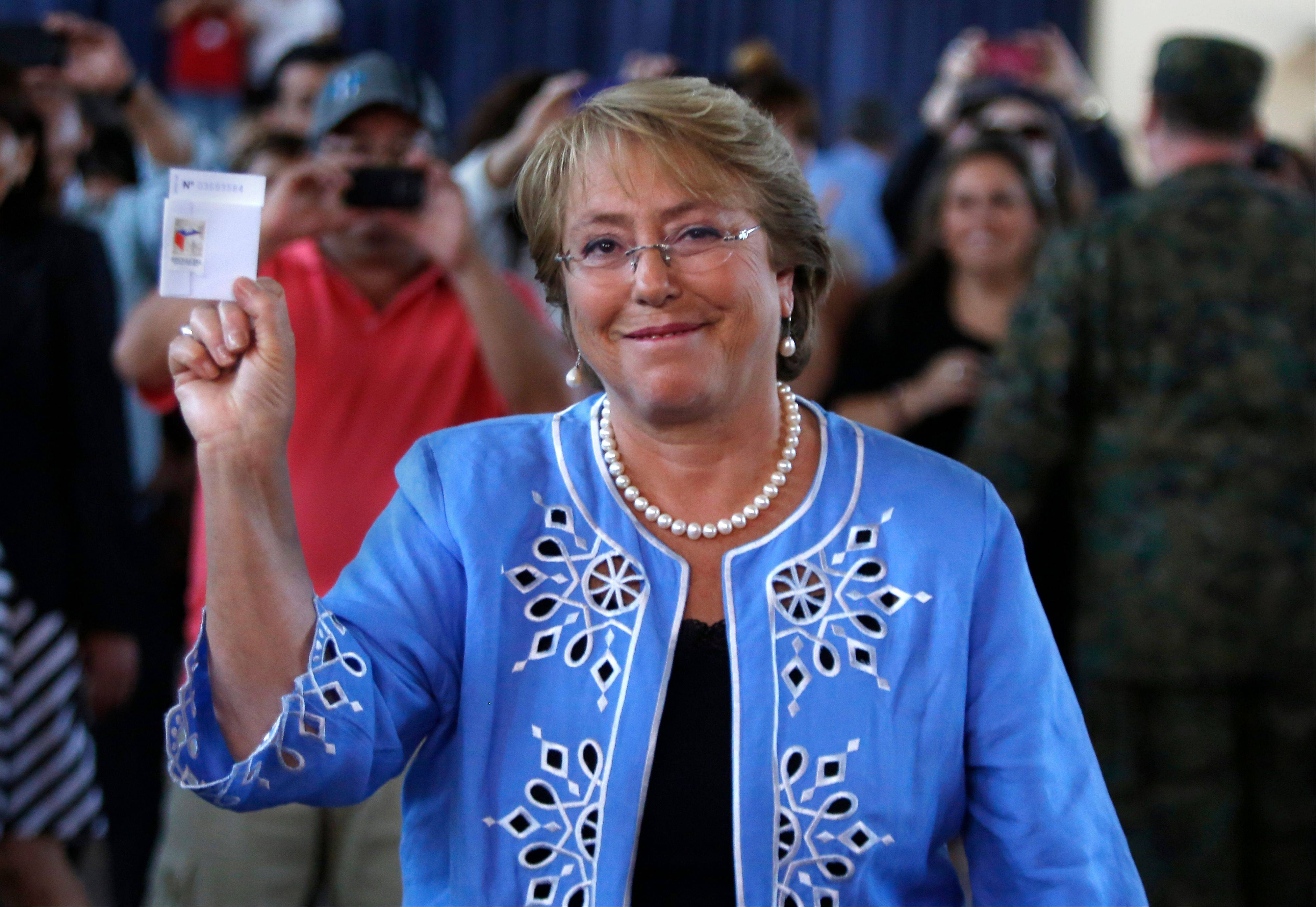 Presidential candidate and former President Michelle Bachelet holds up her ballot before casting it during presidential elections in Santiago, Chile, Sunday. Bachelet easily won re-election, beating conservative rival Evelyn Matthei in Sunday�s runoff vote.