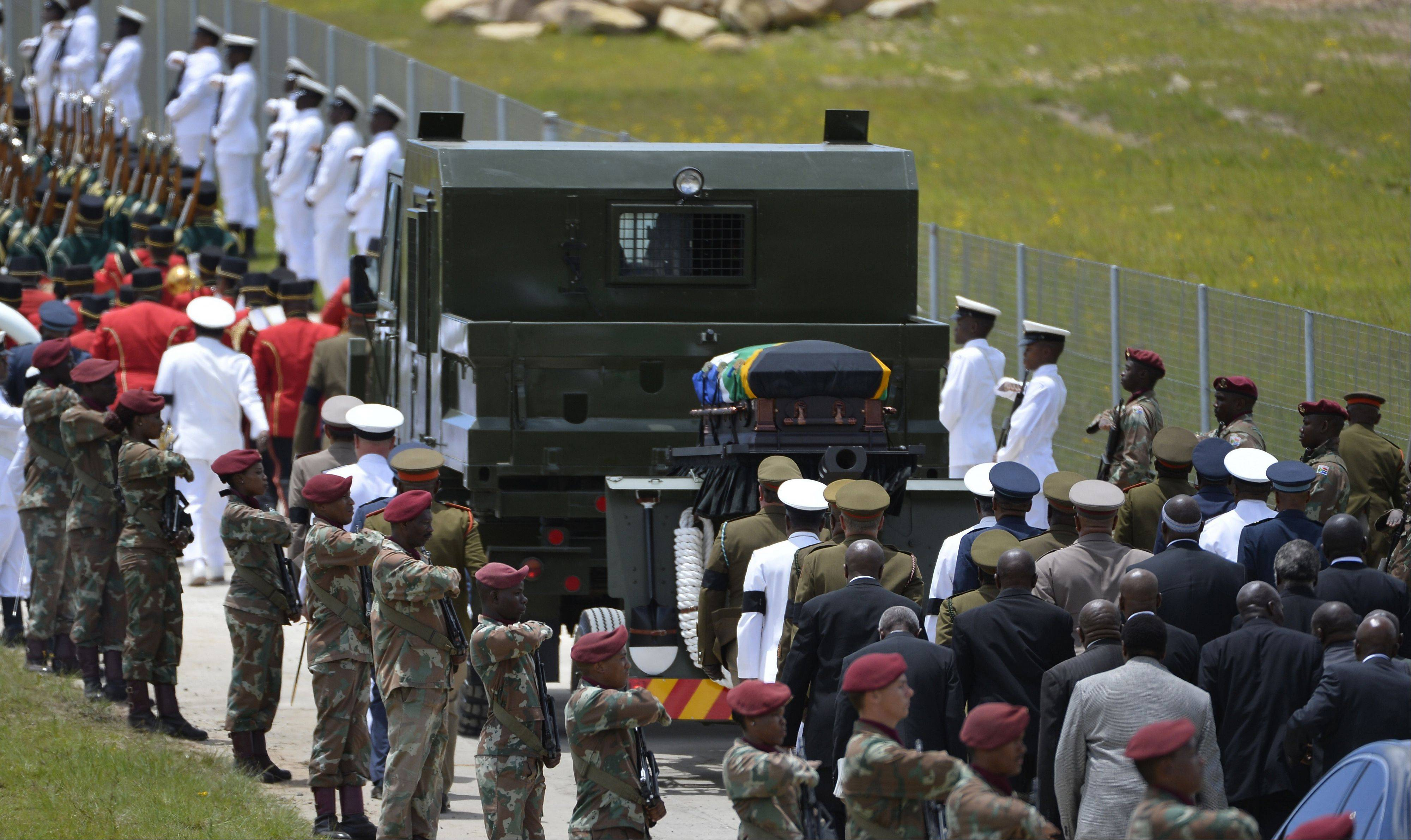 Former South African President Nelson Mandela�s casket is take by military gun carriage to his burial place following his funeral service in Qunu, South Africa, Sunday, Dec. 15, 2013.