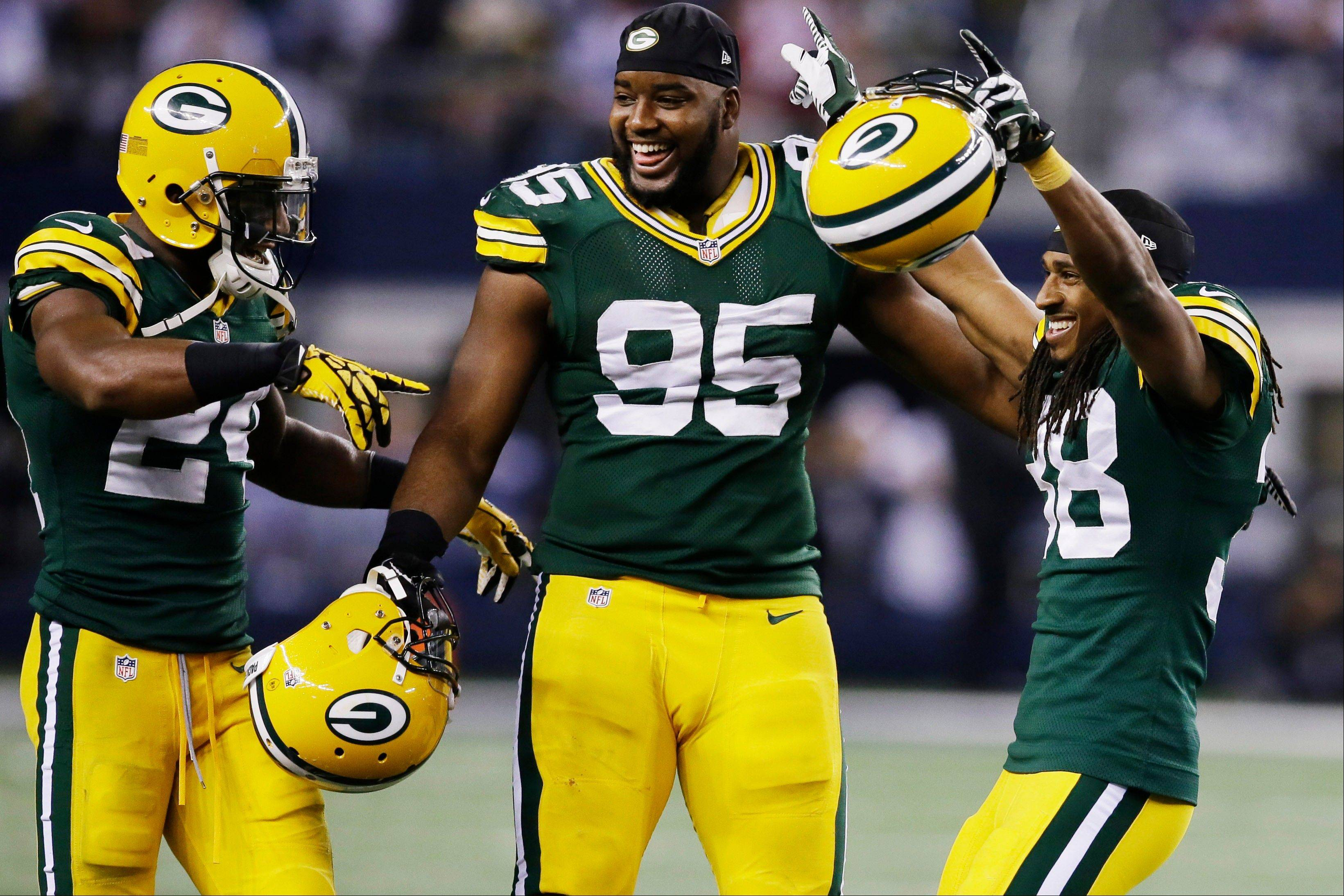 Green Bay Packers cornerback Jarrett Bush (24) defensive end Datone Jones (95) and cornerback Tramon Williams (38) celebrate after beating Dallas Cowboys 37-36 at an NFL football game, Sunday, Dec. 15, 2013, in Arlington, Texas.