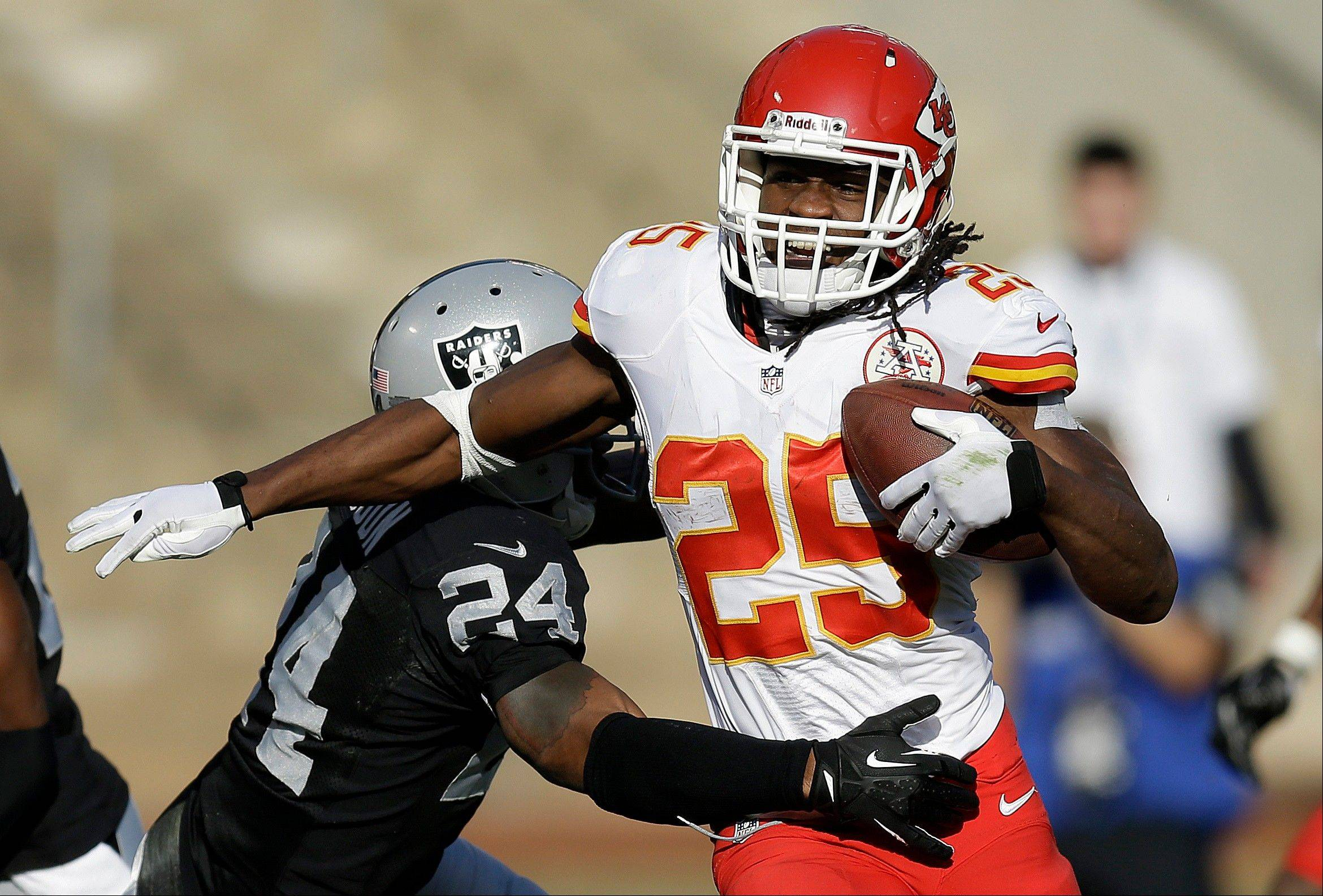 Kansas City Chiefs running back Jamaal Charles (25) runs against Oakland Raiders cornerback Charles Woodson during the second quarter of an NFL football game in Oakland, Calif., Sunday, Dec. 15, 2013.