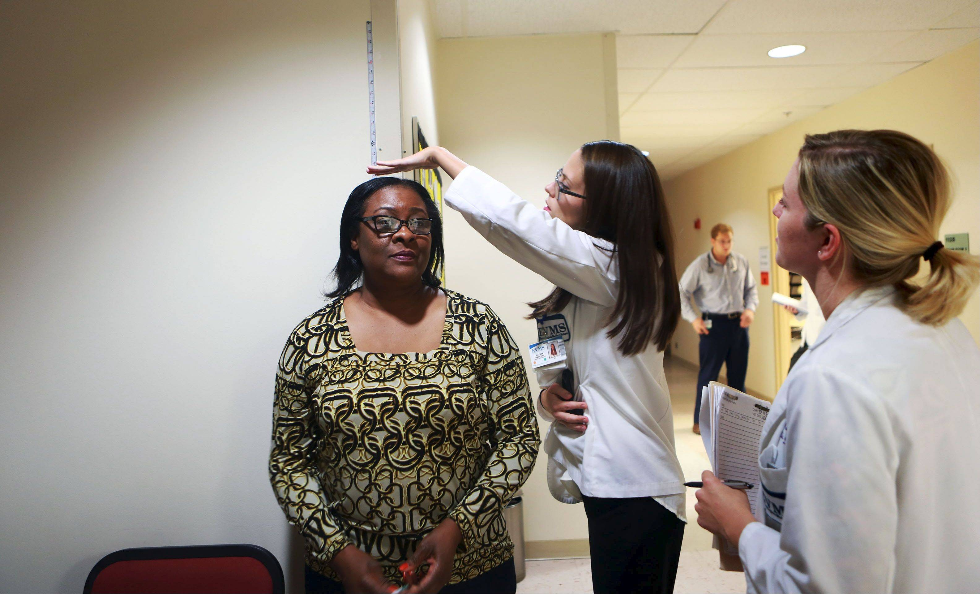 Second-year medical student Alexis Sadecky, center, gathers vitals on patient Donna Eure while Lauren Daugherty looks on at the HOPES women's clinic in Norfolk, Va., the only student-run clinic in Virginia.