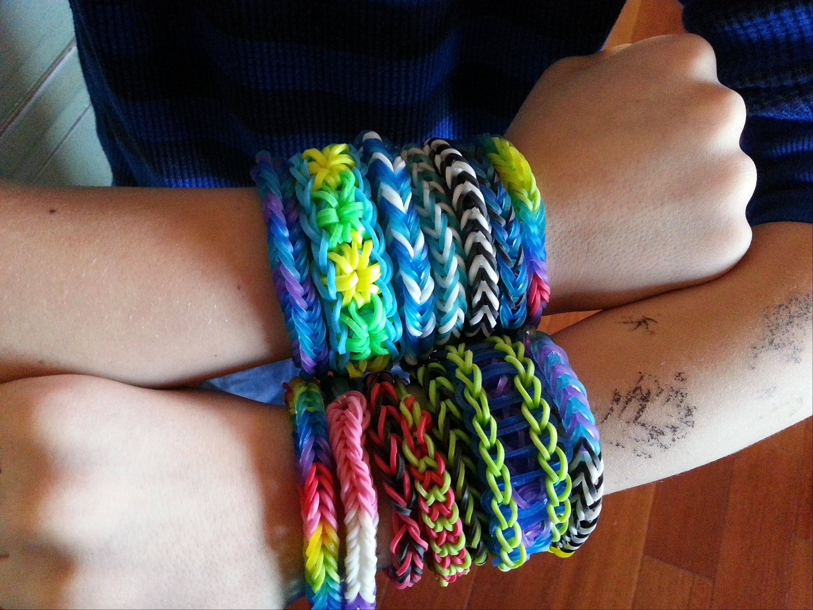Cooper Volkman, 8, shows off the loom band bracelets that he made.