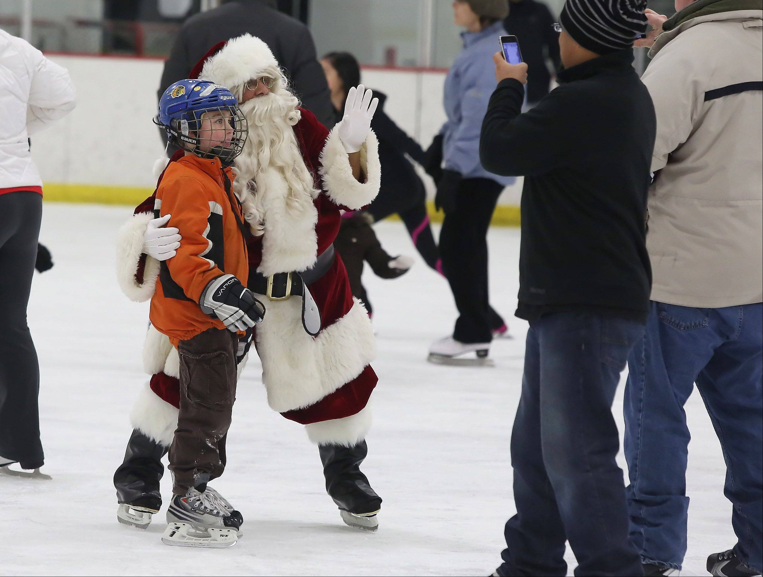 Santa Claus poses for pictures Sunday during Skate with Santa at Triphahn Ice Arena in Hoffman Estates. Families enjoyed open skating with Mr. and Mrs. Claus as well as Frosty the Snowman.
