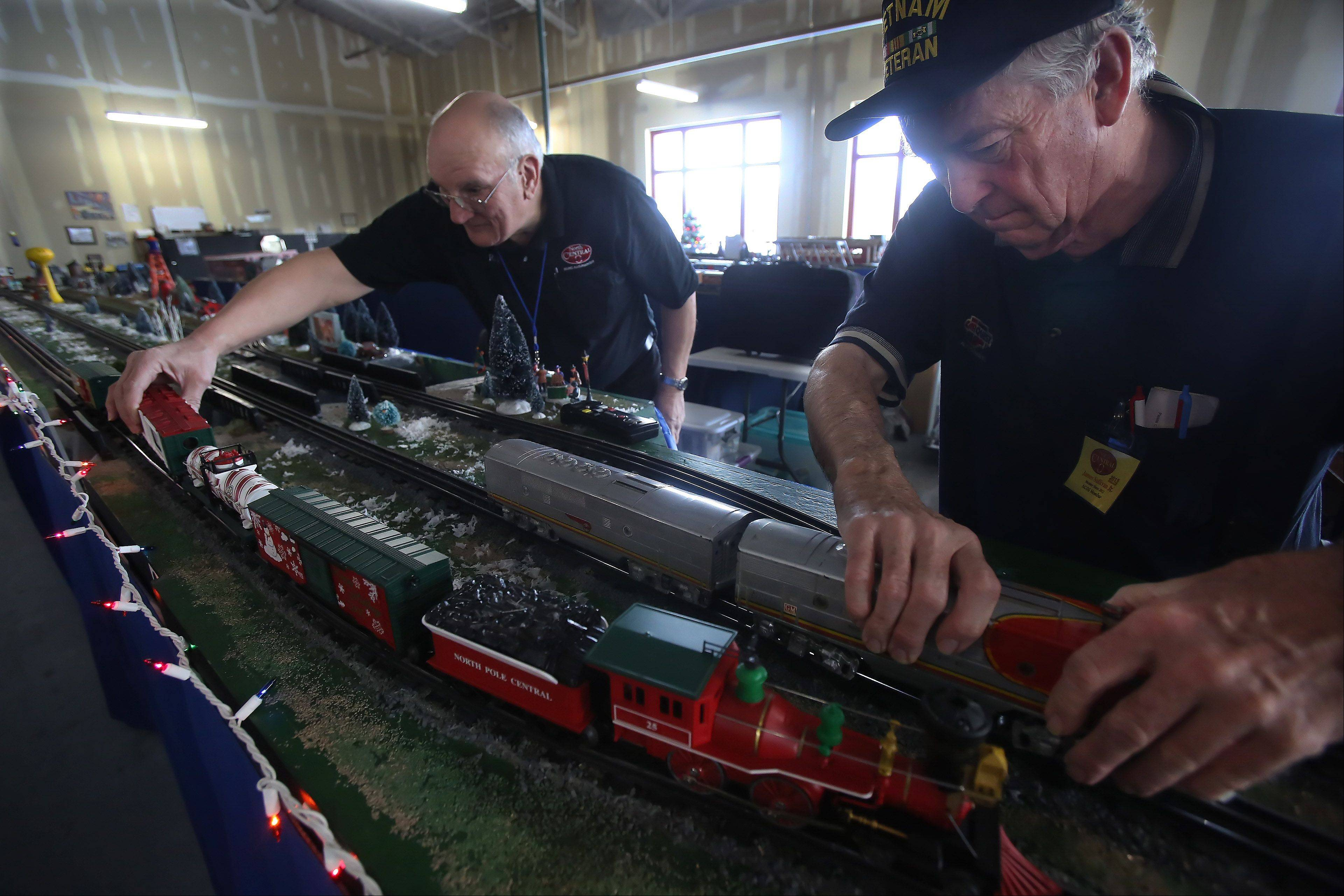 Model railroad operators Rip Paterson of Grayslake, left, and James Sullivan Jr. of Highland Park set up the North Pole Central during a Christmas-themed model train display Sunday at Fremont Public Library in Mundelein. The event was sponsored by the North Central O Gaugers Model Railroad Club, Inc. Children and families watched as trains passed by snow-covered towns and holiday crowds.