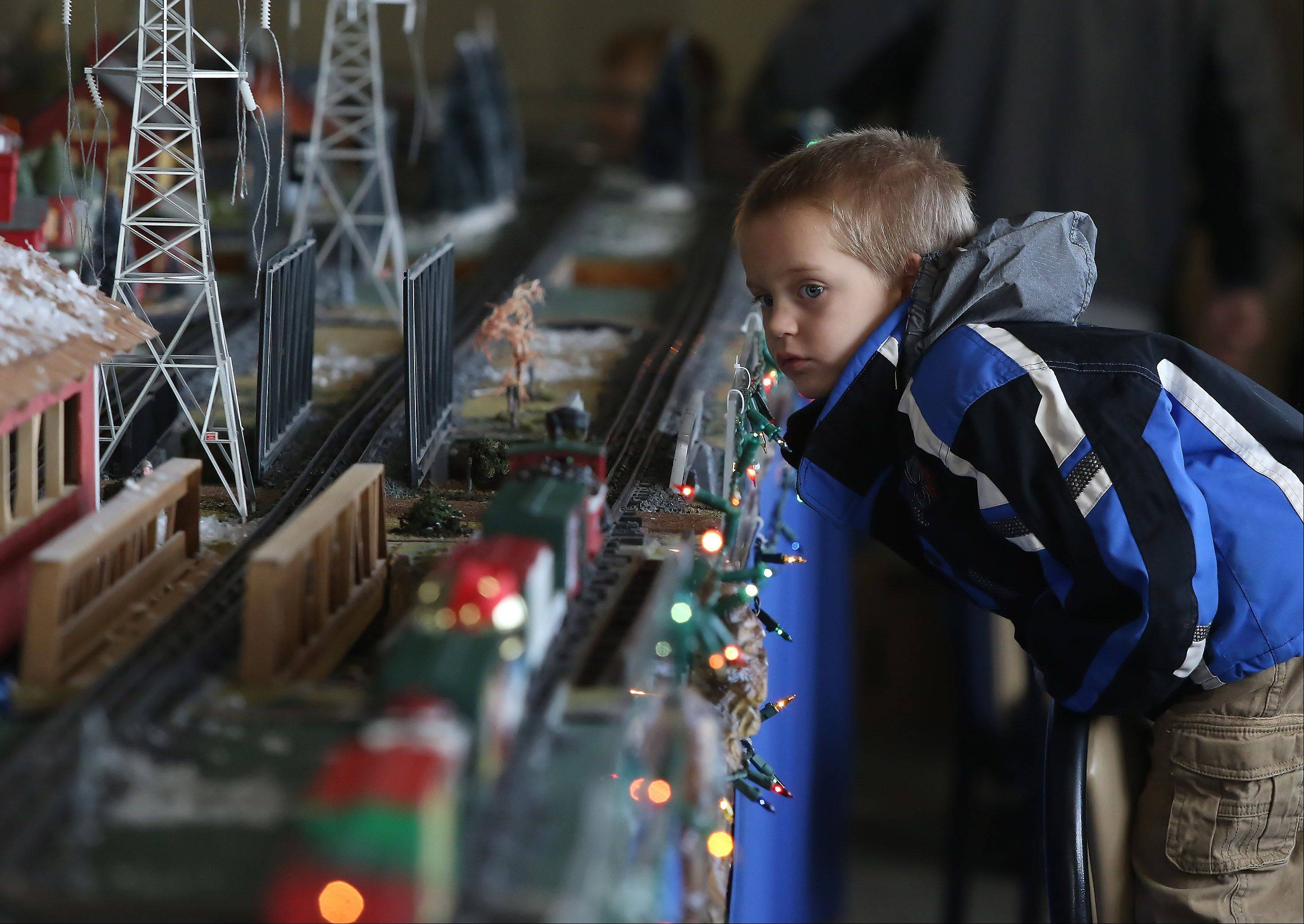 Four-year-old Mason McMurray of Mundelein watches trains go by during a Christmas-themed model train display Sunday at Fremont Public Library in Mundelein. The event was sponsored by the North Central O Gaugers Model Railroad Club, Inc. Children and families watched as trains passed by snow-covered towns and holiday crowds.