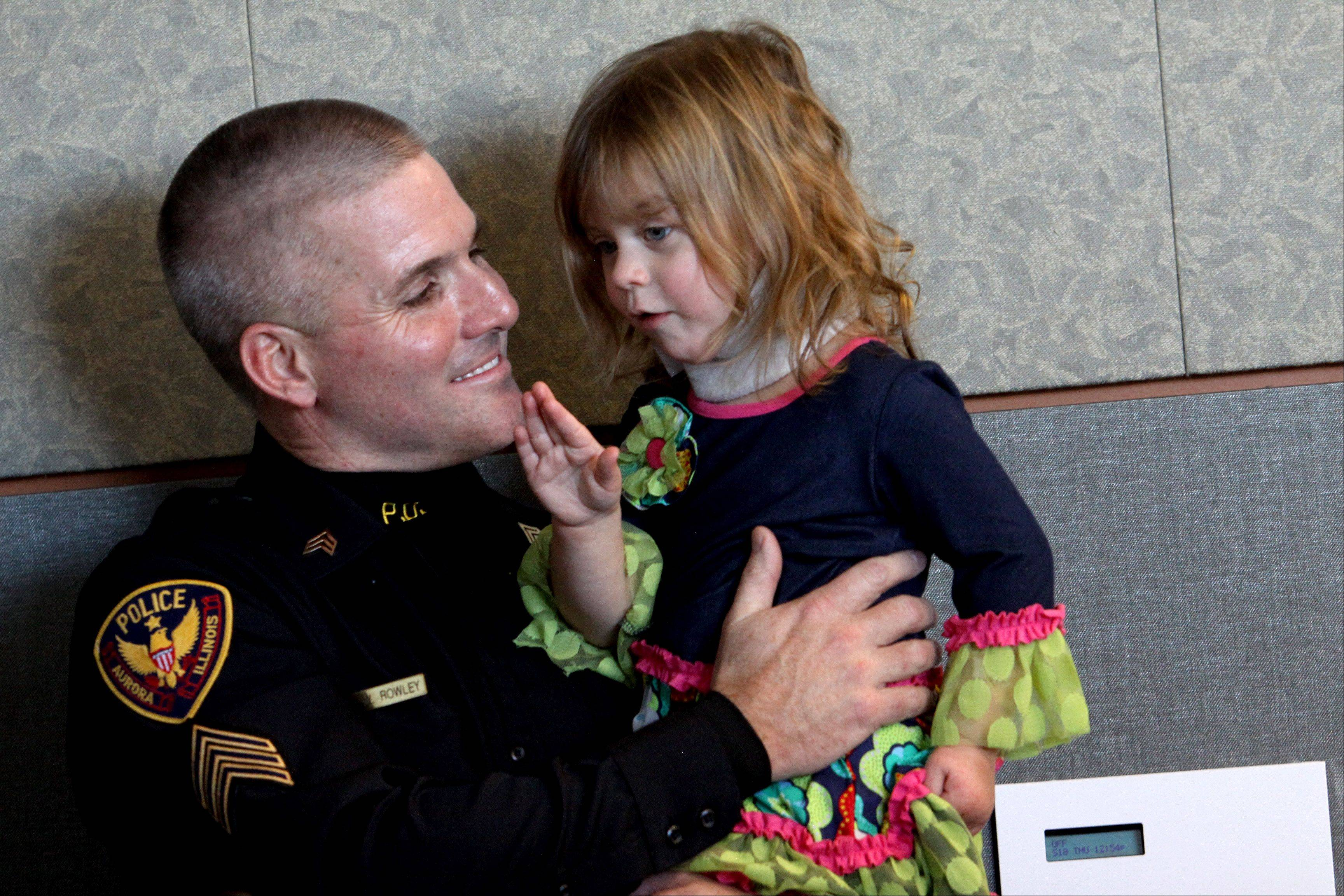 Sgt. Bill Rowley holds Abigail Schmidt, 2, at the Aurora Police Station on Thursday. He saved her life in October when he was off-duty and both their families were heading toward a pumpkin patch near Joliet. The vehicle in which the little girl was riding was struck by another car and she likely would have died if he had not give her CPR.