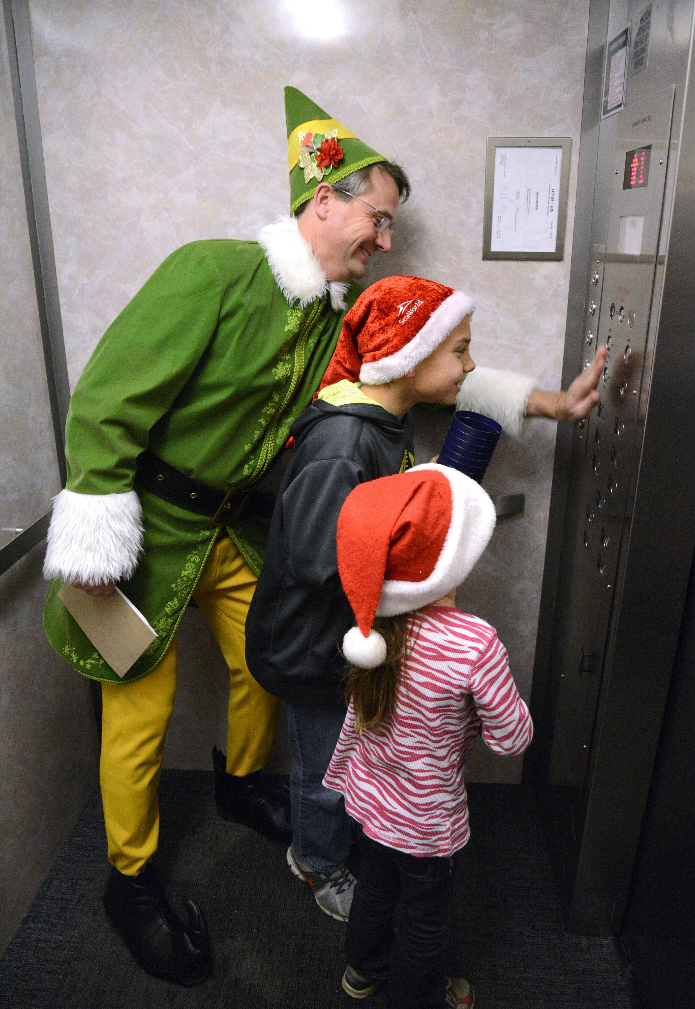 "Judson University president Gene Crume stays in character as Buddy the Elf and his helpers Caden Pearl, 10, of Elgin and sister Allison, 7, press all the buttons on the elevator on their trip to deliver milk and cookies to students during the annual ""Storm the Dorms"" on Wednesday, December 11."