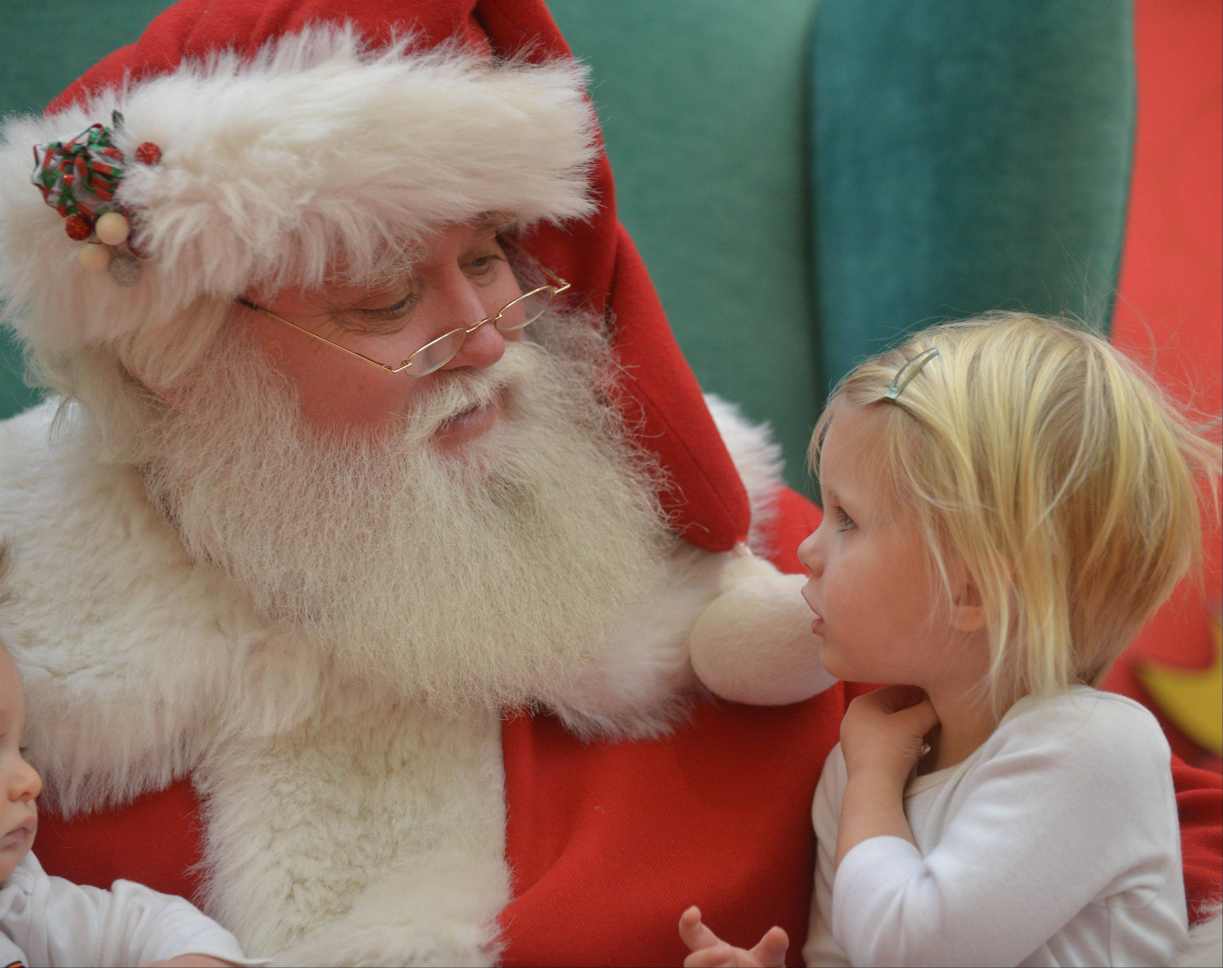 Santa has a chat with Sri Rose Richardson, 2, of Elmhurst about what she wants for the holidays while on duty at Yorktown Center Thursday.