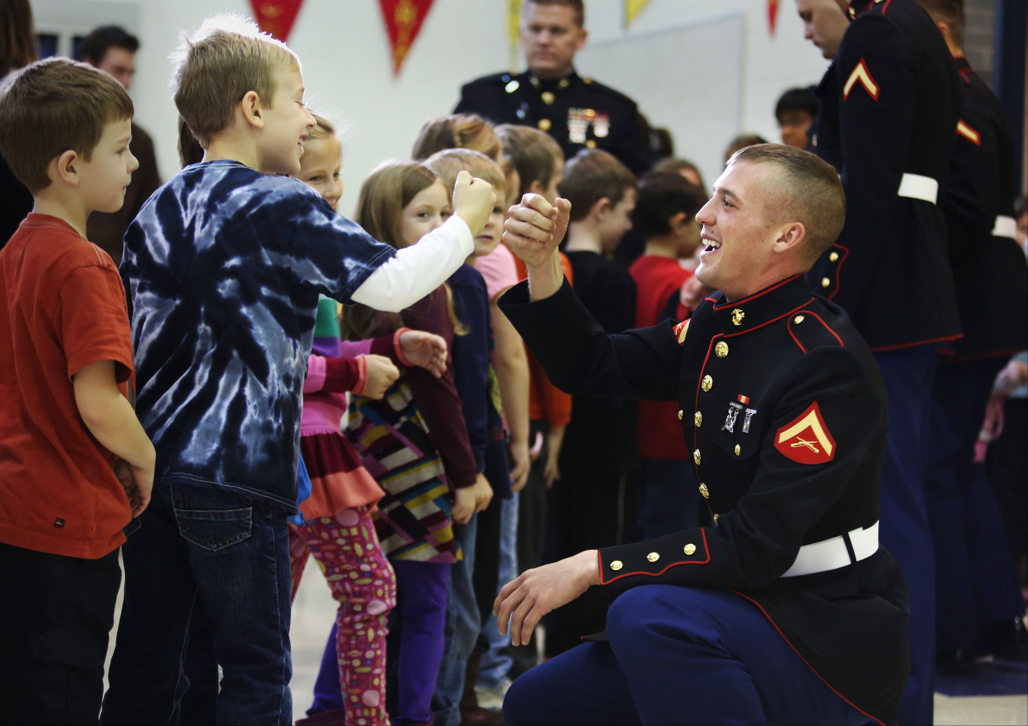 Lance Cpl. Jordan Patrick gets an enthusiast fist bump from Grace McWayne first-grader Gavin Rosengren Friday morning at the school. The students at the school collected over 700 toys for the Toys for Tots program which will be distributed to children throughout Kane County. Patrick is from Oswego, and currently stationed in Twentynine Palms, California.