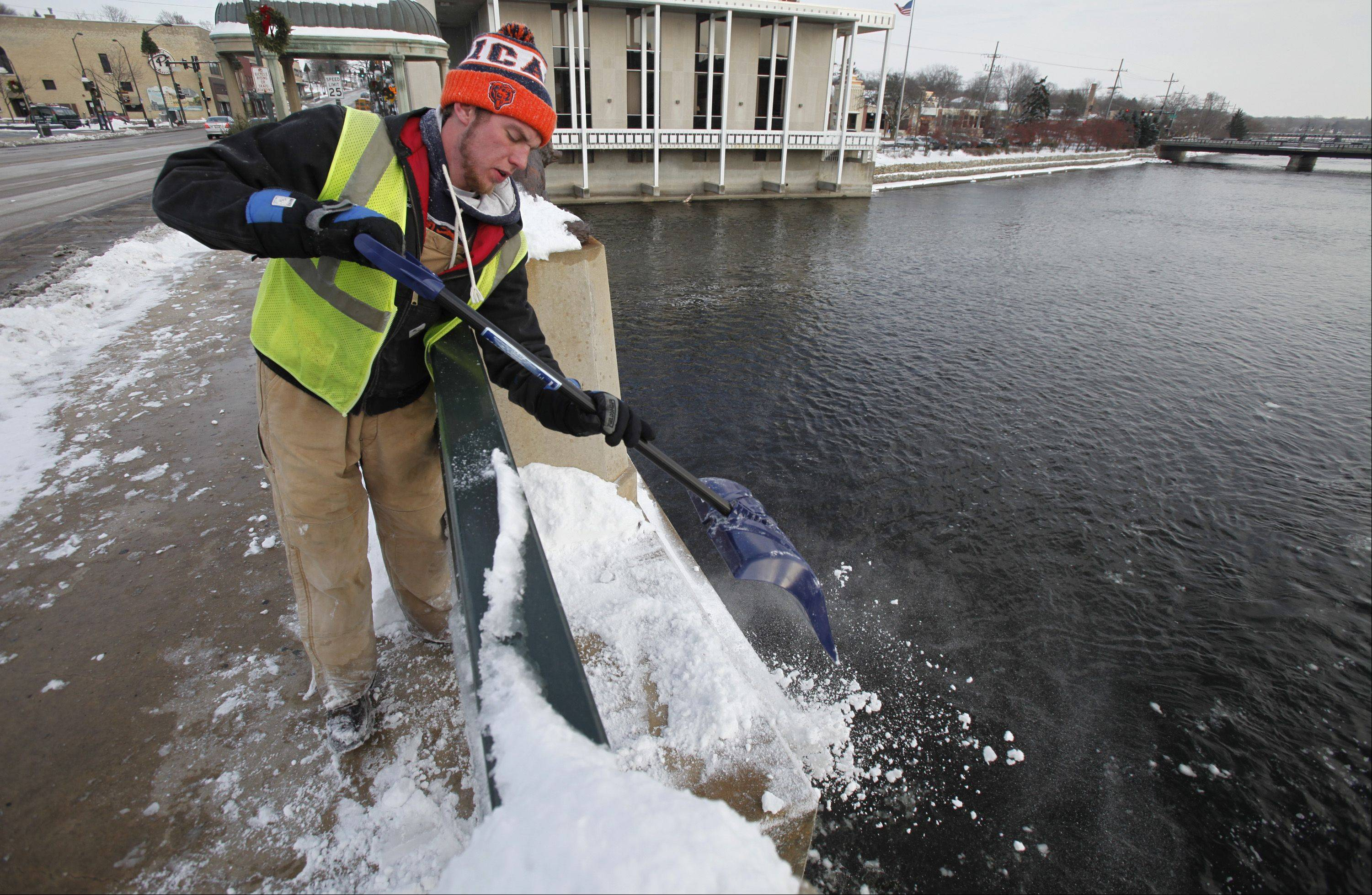 Brian Kus, of Batavia, helps clear snow from the Main Street bridge in downtown St. Charles Monday. Kus said he had been out working since 7:30 a.m. and definitely felt the temperature dropping throughout the day. Kus was working to fulfill service hours for the community restitution program.