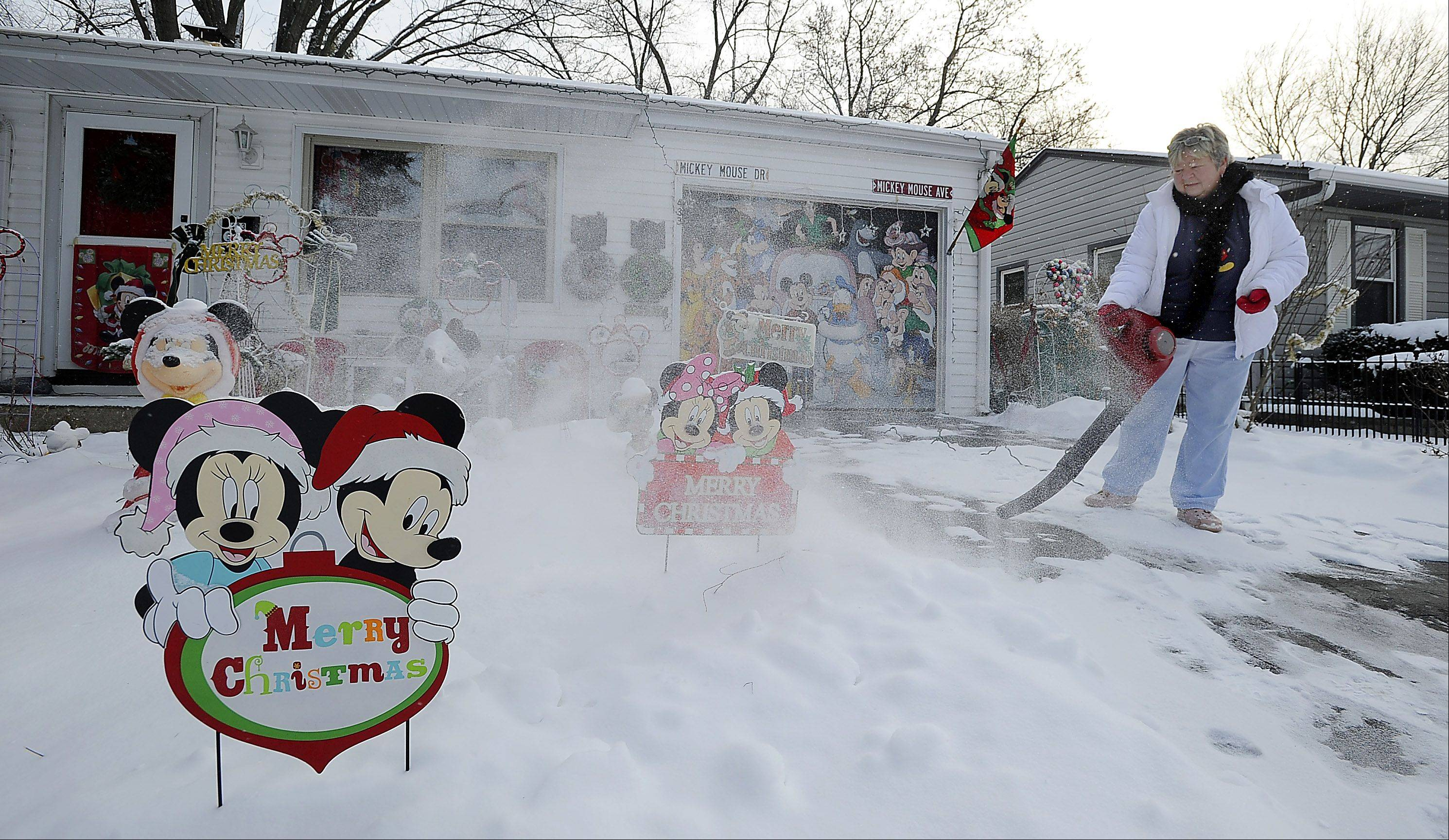 Teri Anderson, of Buffalo Grove, uses her leaf blower to clean off the fresh coating of snow that fell overnight as Walt Disney's characters keep her company.