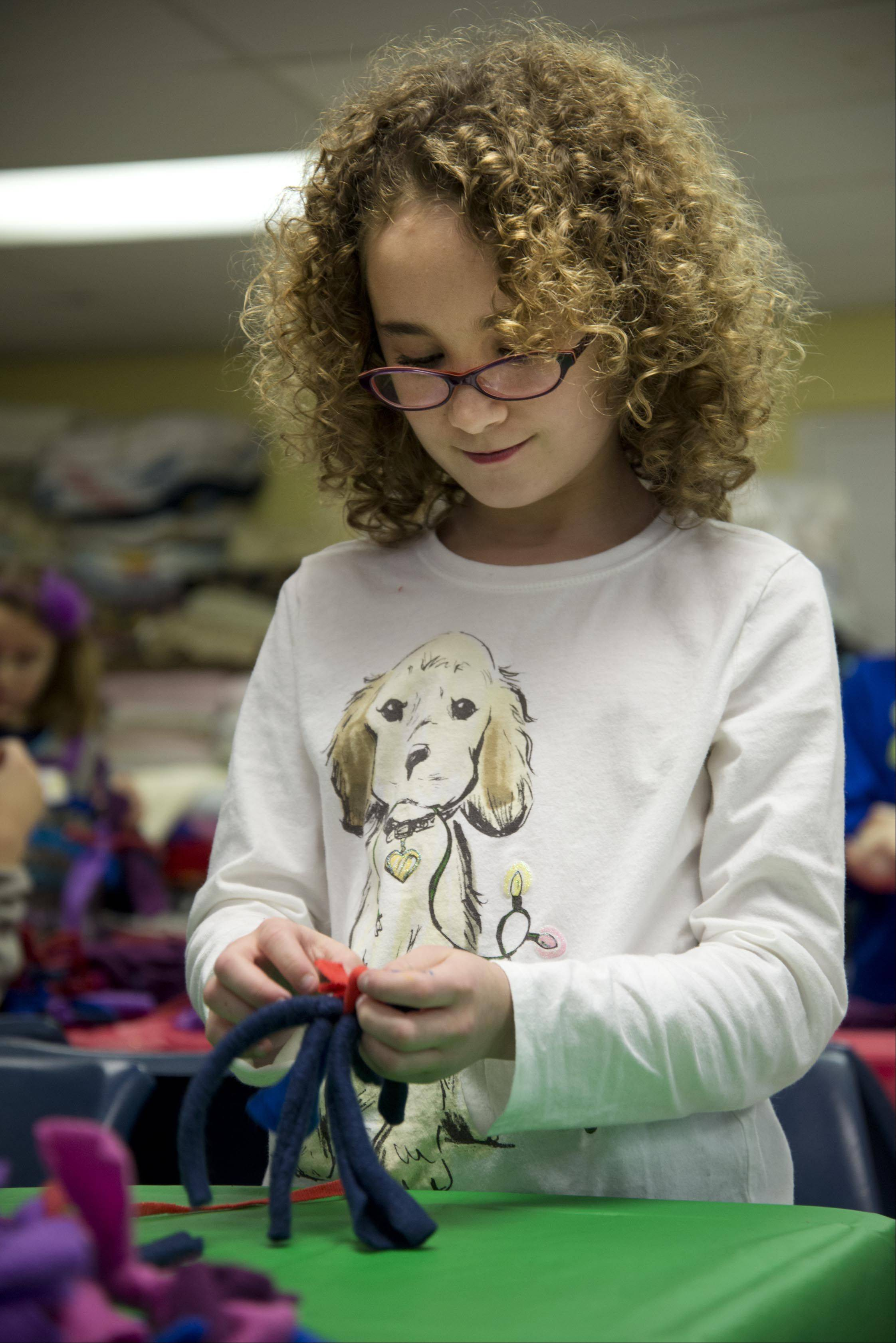 "Payton Smith, 10, of St. Charles, makes a felt cat toy Sunday during the Santa Paws Workshop For Kids at the Anderson Animal Shelter in South Elgin. ""I love this place,"" she said. ""It's very fun."""