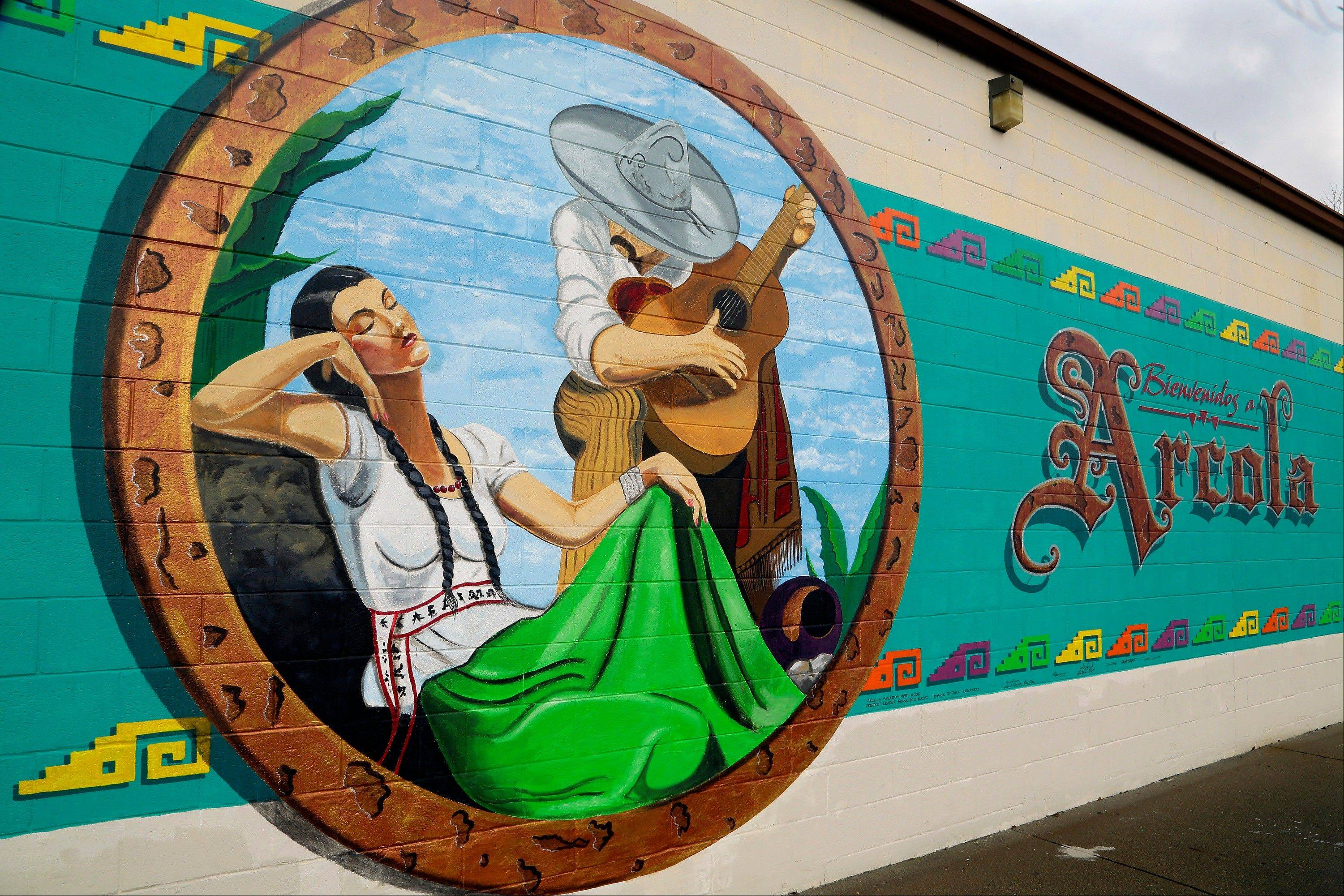 A Hispanic-themed mural is seen on the side of a building in Arcola, Ill., in Douglas County. Douglas has both a large Hispanic population and Amish population. Hispanics in the U.S. are more likely to be uninsured than the rest of the population _ about 31 percent lack health coverage, according to the U.S. Centers for Disease Control. Douglas is second only to Cook County in percentage of Illinoisans without health insurance.