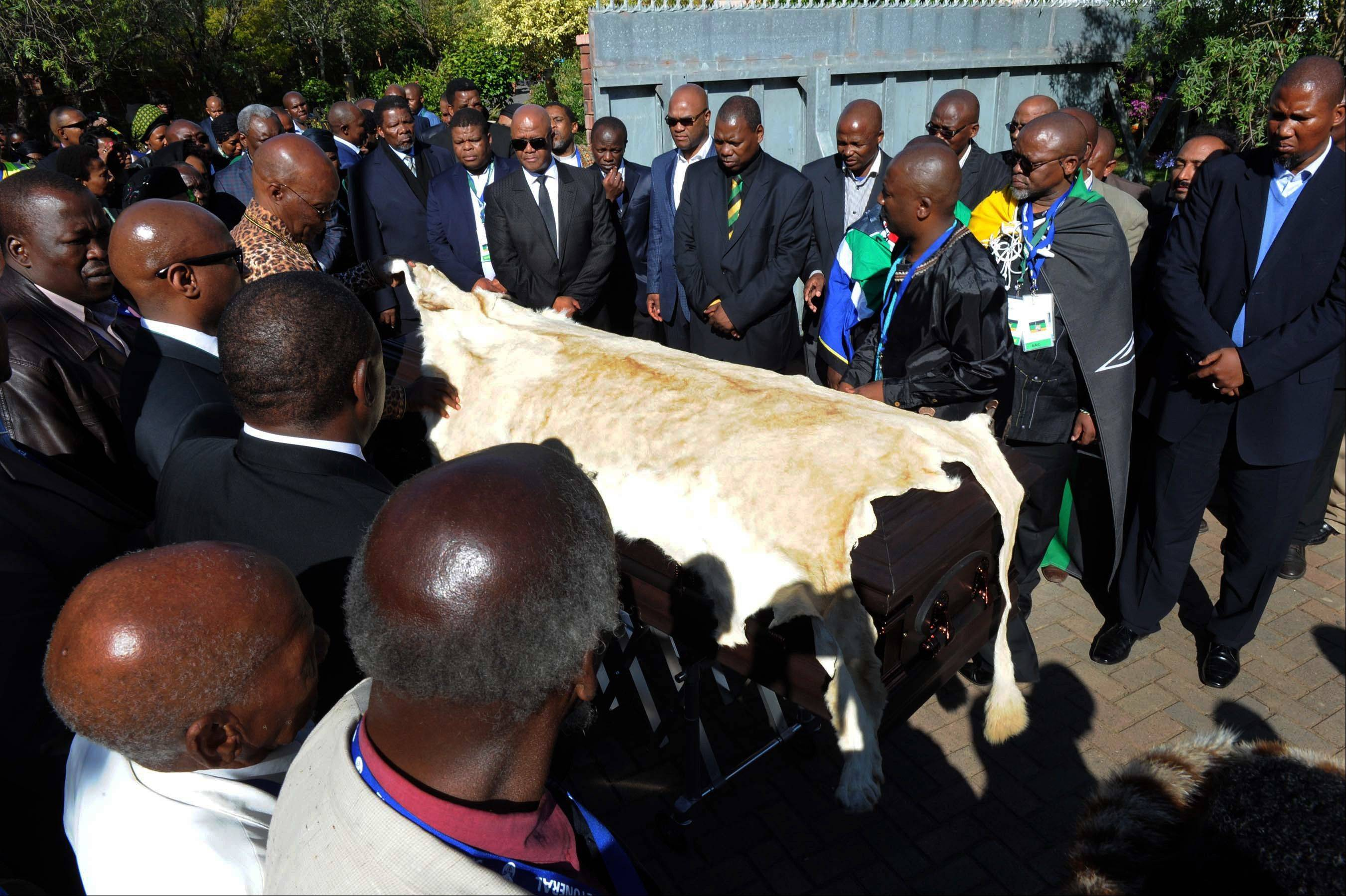 Nelson Mandela's grandson Mandla Mandela, right, watches as local chiefs drape the casket of former South African President Nelson Mandela with a lion skin as it arrives at the Mandela residence in Qunu, South Africa, Saturday.