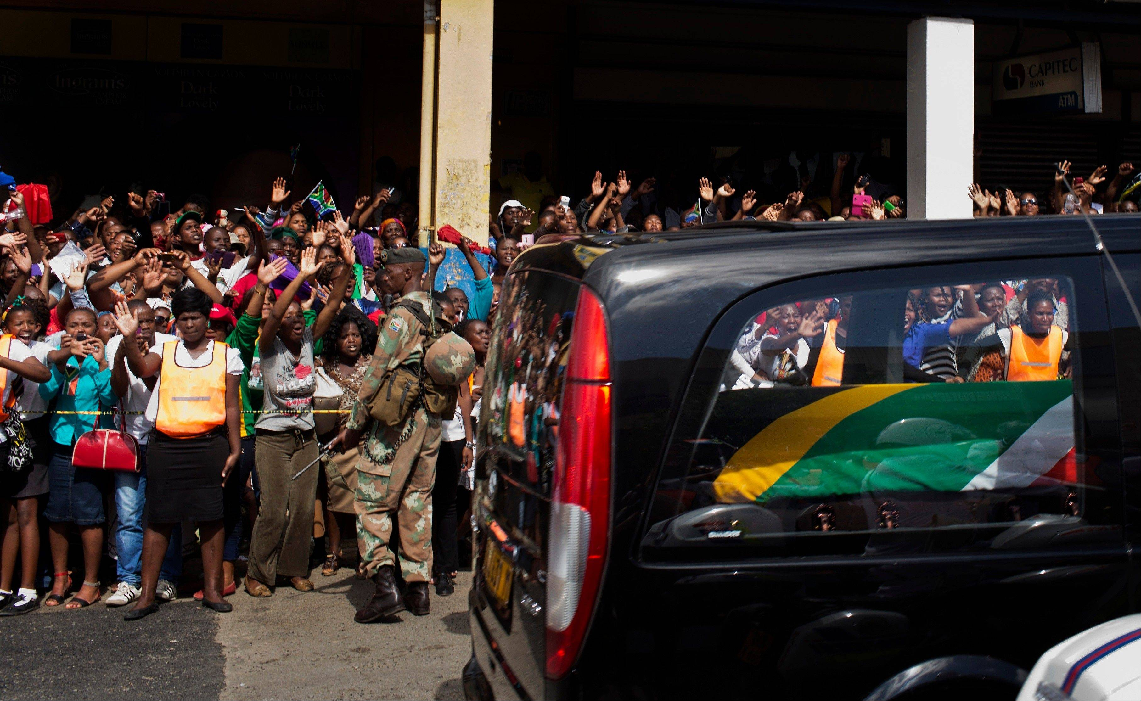 The motorcade transporting the body of Nelson Mandela, in black hearse, passes through crowds of mourners gathered in the town of on its way to Qunu, South Africa Saturday, Dec. 14, 2013.