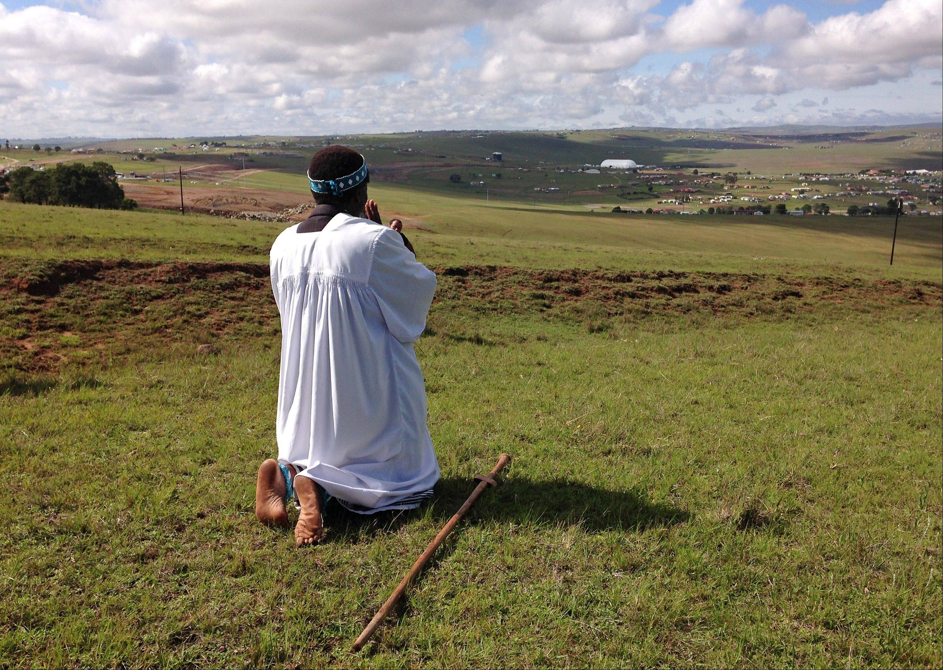 Shembe priest Michael Notychanga prays in the direction of the home of former South African President Nelson Mandela on a hill where in the distance you can see the dome where his funeral service takes place in Qunu, South Africa, Sunday, Dec. 15, 2013.