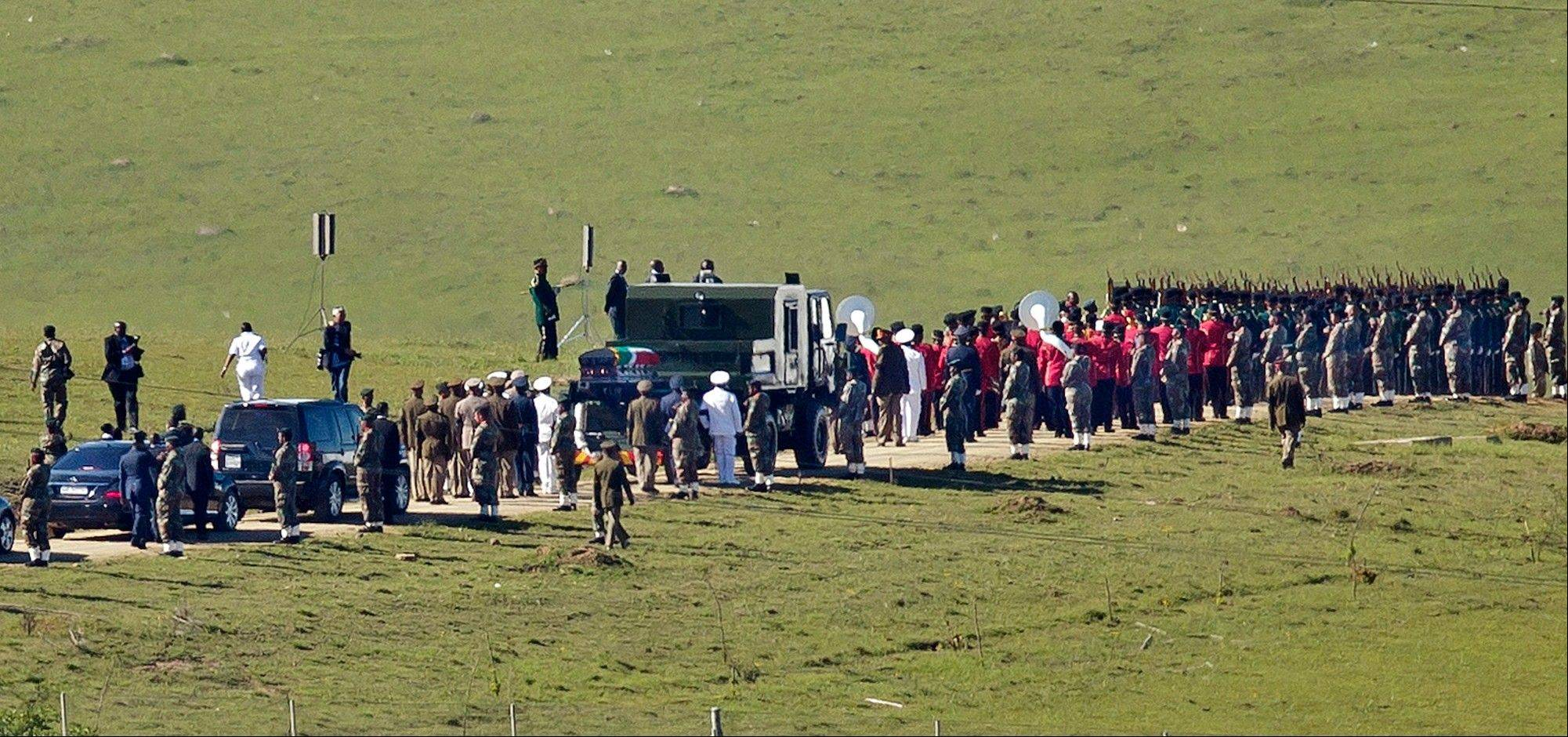 The casket of Nelson Mandela is brought in a military parade on a gun carriage from the family home to the funeral tent, prior to his burial, in Qunu, South Africa Sunday, Dec. 15, 2013.