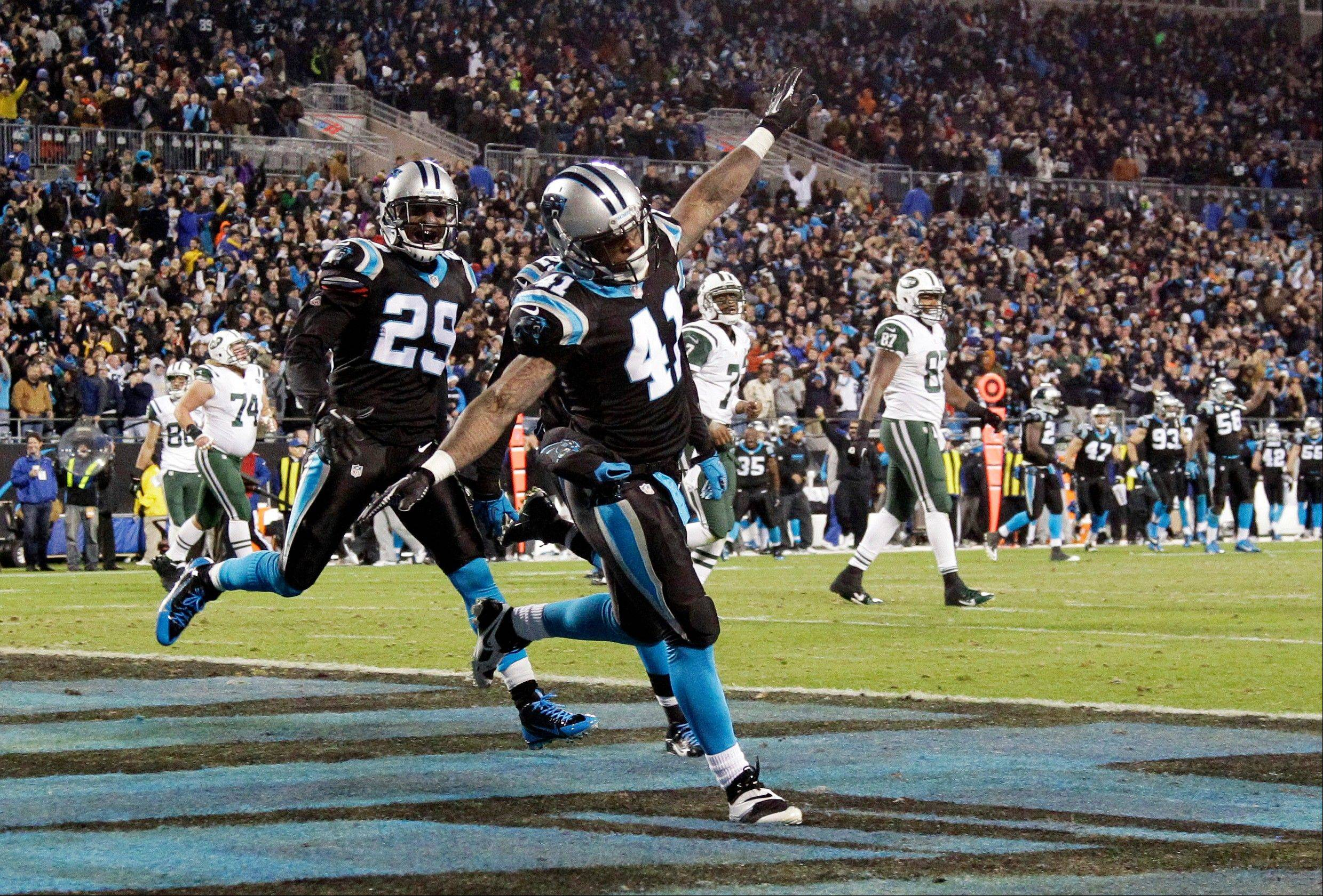 Carolina Panthers' Captain Munnerlyn (41) celebrates his interception return for a touchdown with Drayton Florence (29) during the second half of an NFL football game against the New York Jets in Charlotte, N.C., Sunday, Dec. 15, 2013.