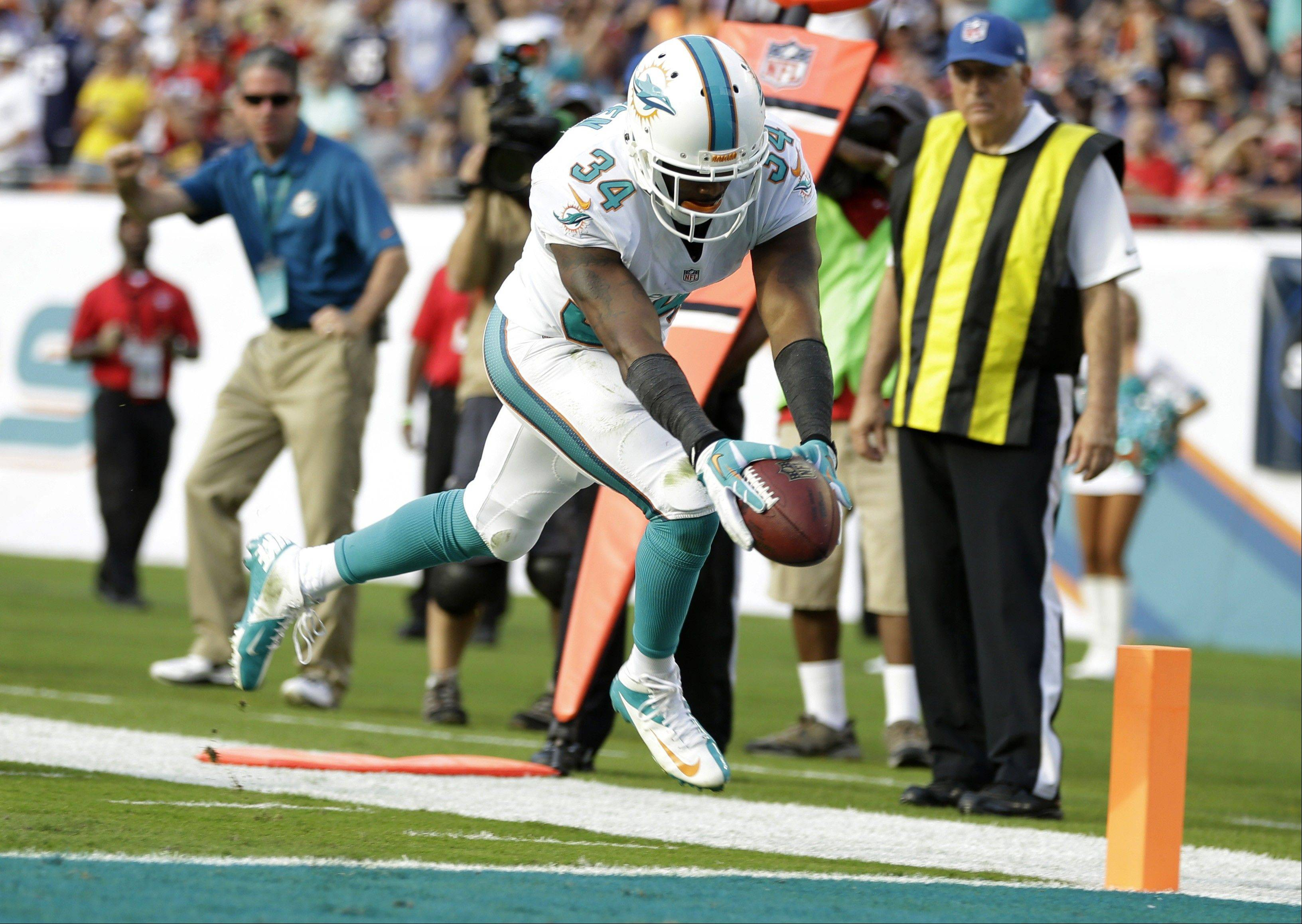 Miami Dolphins running back Marcus Thigpen (34) scores a touchdown during the second half of an NFL football game against the New England Patriots, Sunday, Dec. 15, 2013, in Miami Gardens, Fla.
