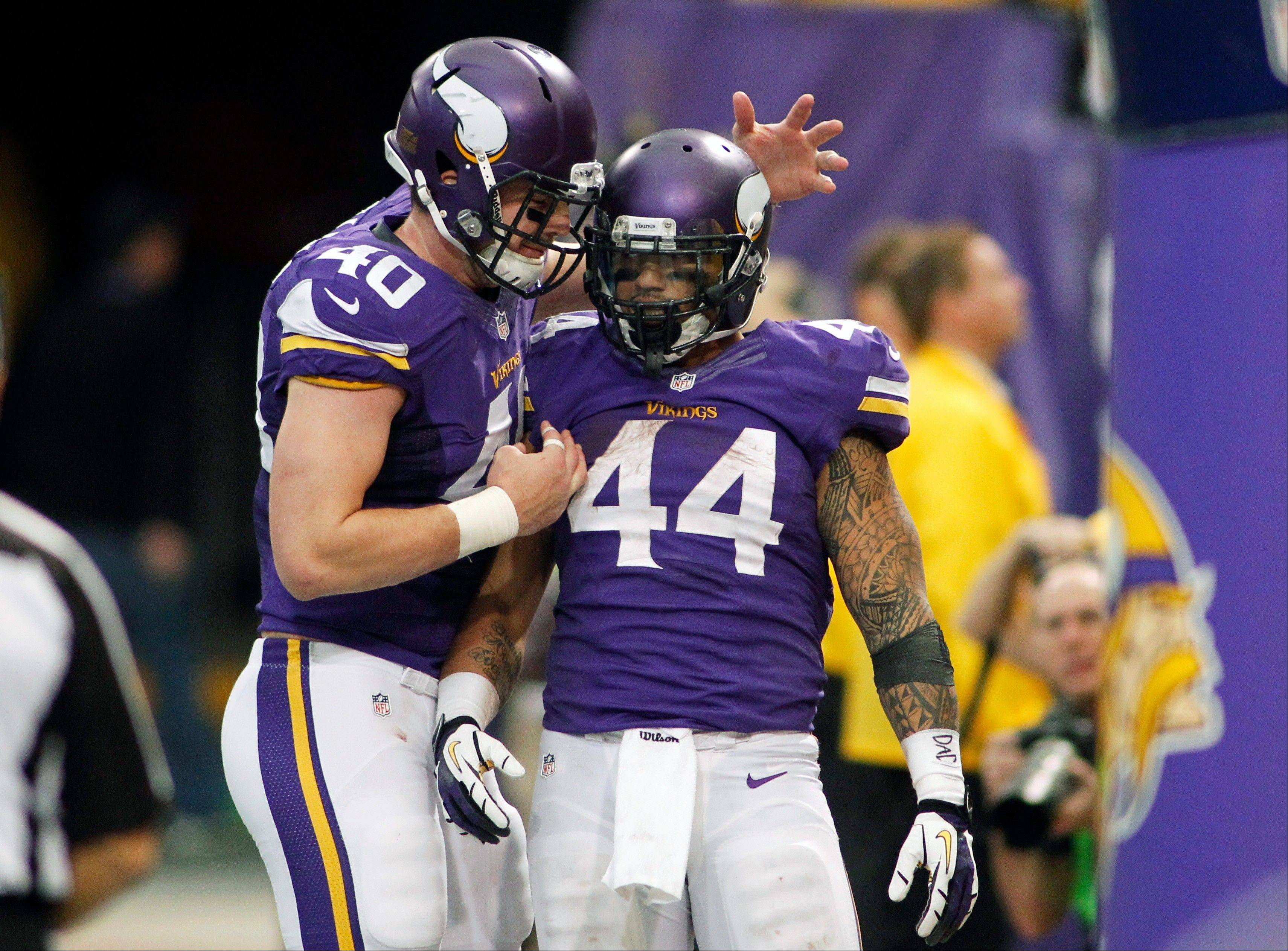 Minnesota Vikings running back Matt Asiata (44) celebrates with teammate Rhett Ellison after scoring on a 1-yard touchdown run during the second half of an NFL football game against the Philadelphia Eagles, Sunday, Dec. 15, 2013, in Minneapolis.