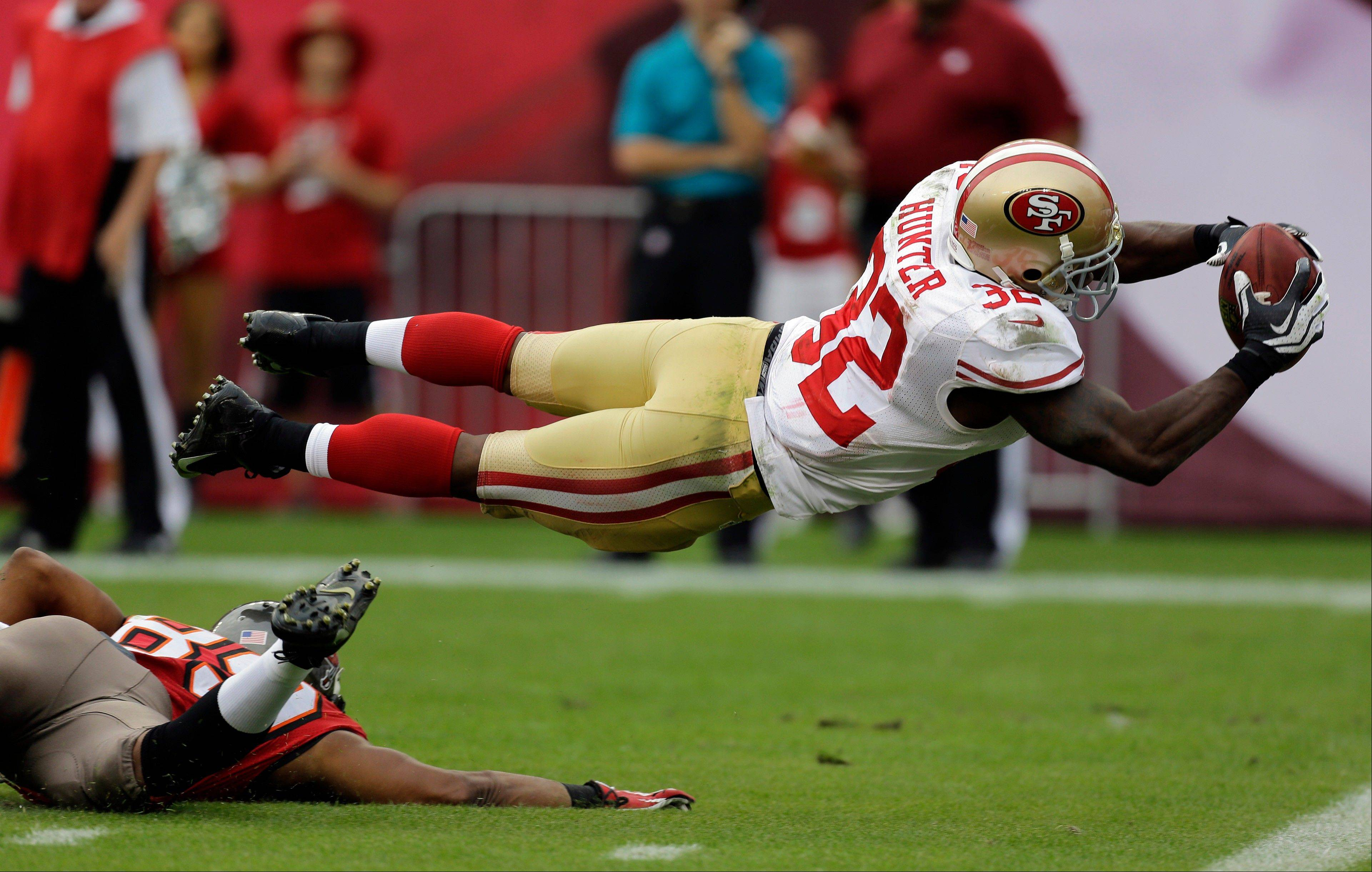 San Francisco 49ers' Kendall Hunter (32) dives into the end zone to score after picking up a fumble by Tampa Bay Buccaneers' Russell Shepard during the fourth quarter of an NFL football game Sunday, Dec. 15, 2013, in Tampa, Fla.