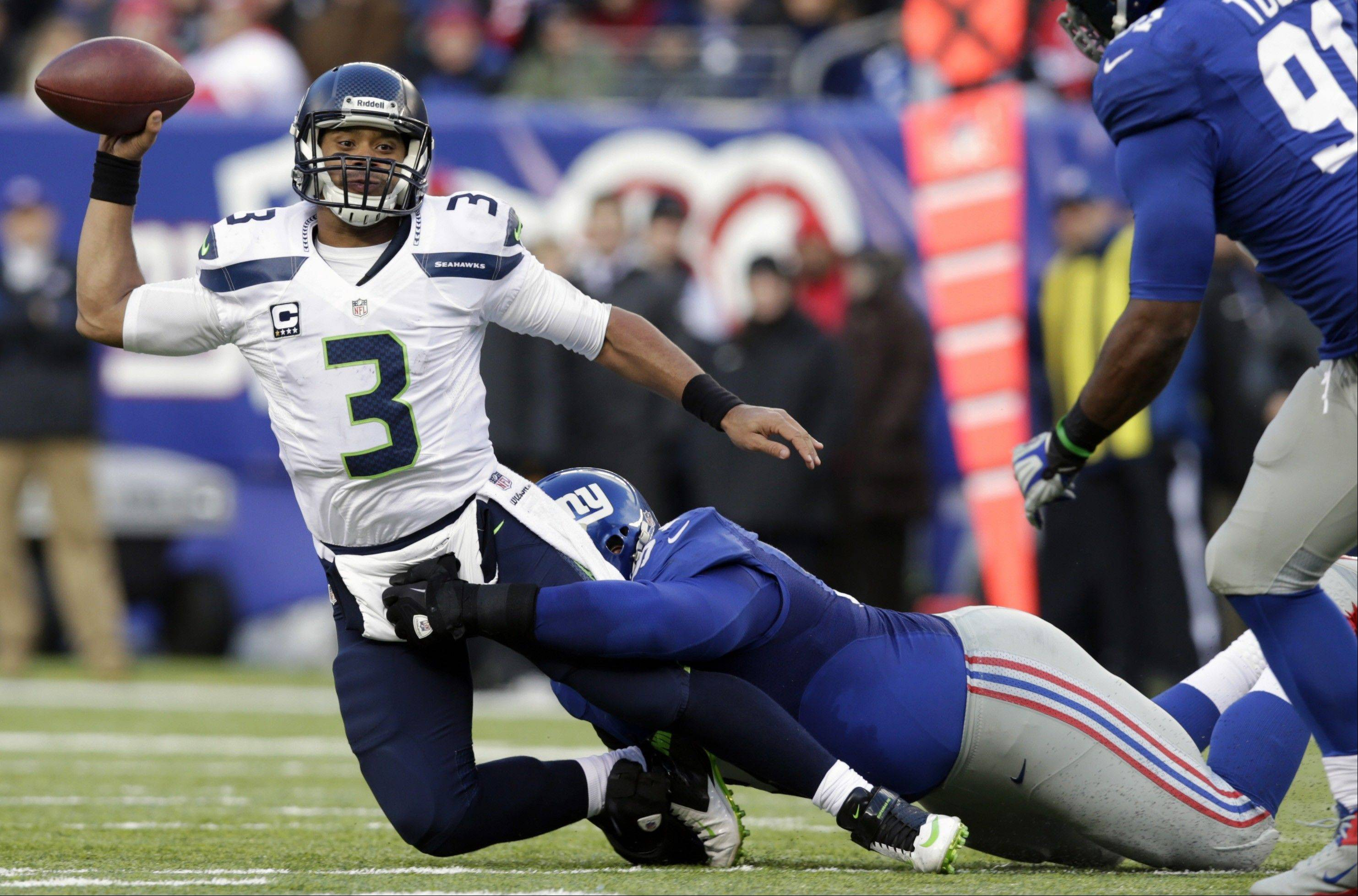 Seattle Seahawks quarterback Russell Wilson (3) is sacked by New York Giants defensive tackle Linval Joseph during the first half of an NFL football game, Sunday, Dec. 15, 2013, in East Rutherford, N.J.