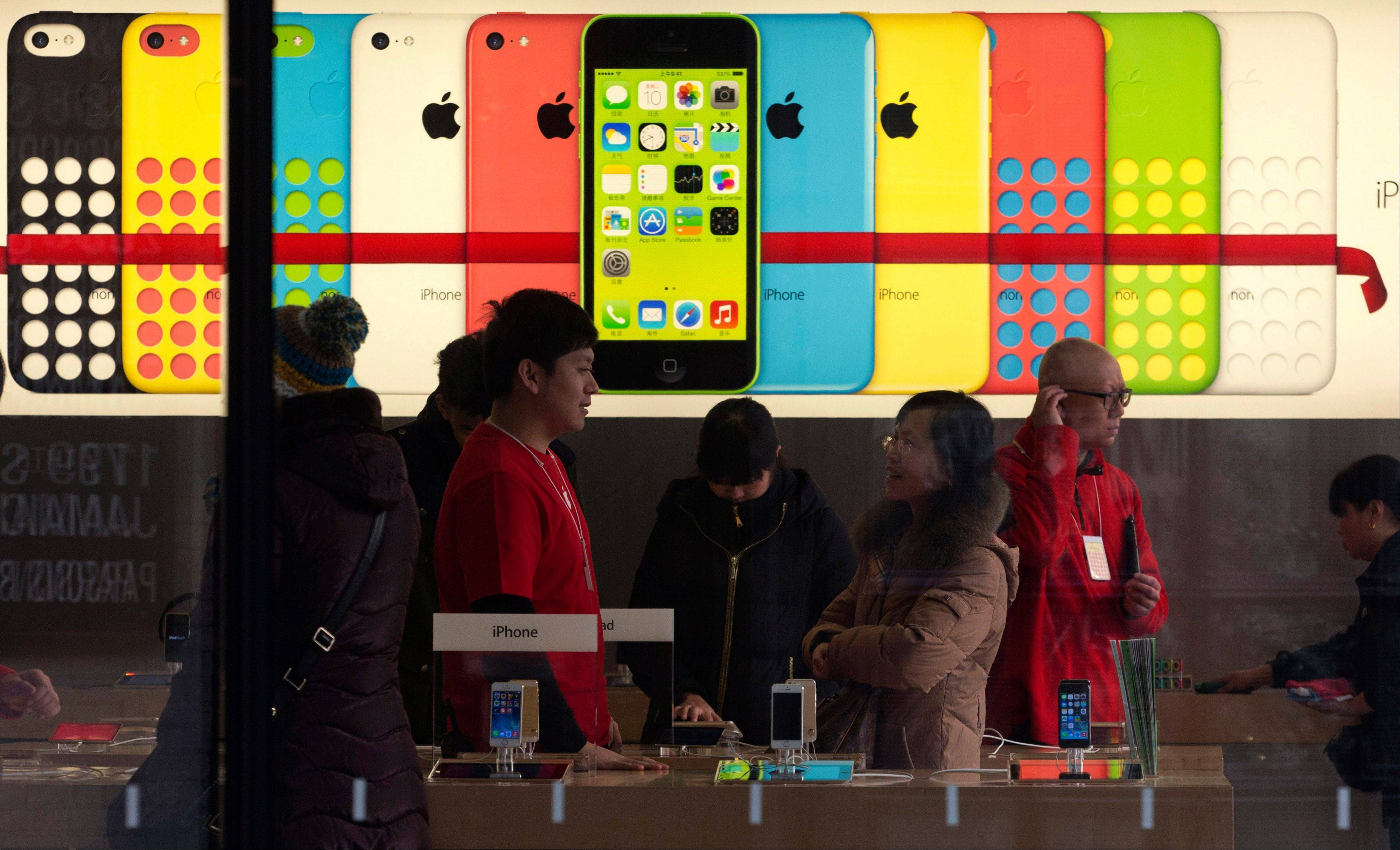 A woman talks to a salesperson in front of an advertisement for iPhones at Apple�s retail store in Beijing Monday. Apple Inc. might have a chance to pep up cooling iPhone sales in China if it finally can reach a deal with the world�s biggest phone carrier.