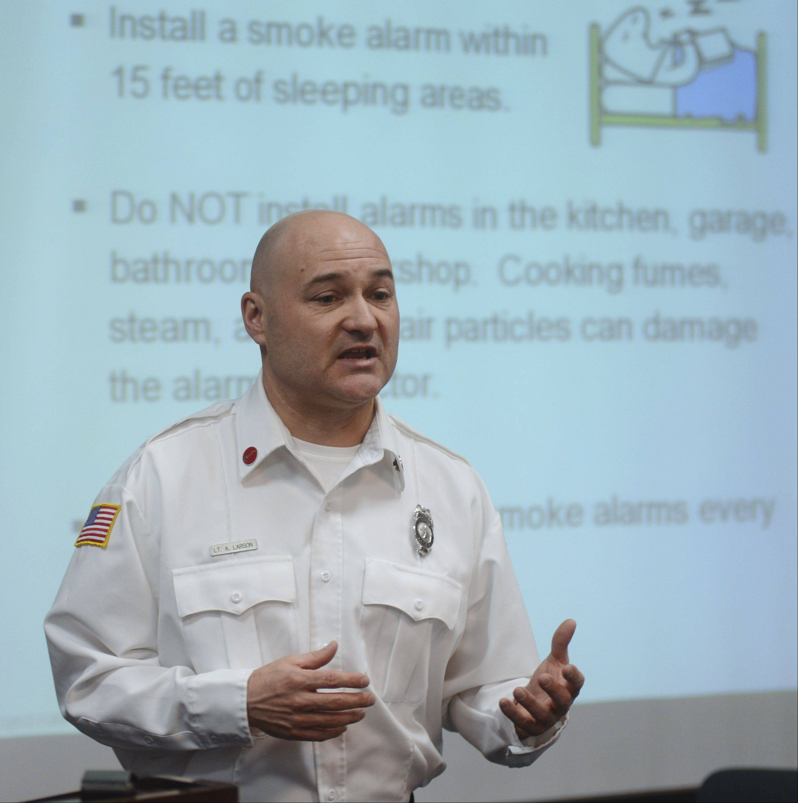 Lt. Andrew Larson talks about proper placement of smoke alarms, as volunteers prepare to help assure that there are working devices in the homes of senior citizens who signed up for the program.