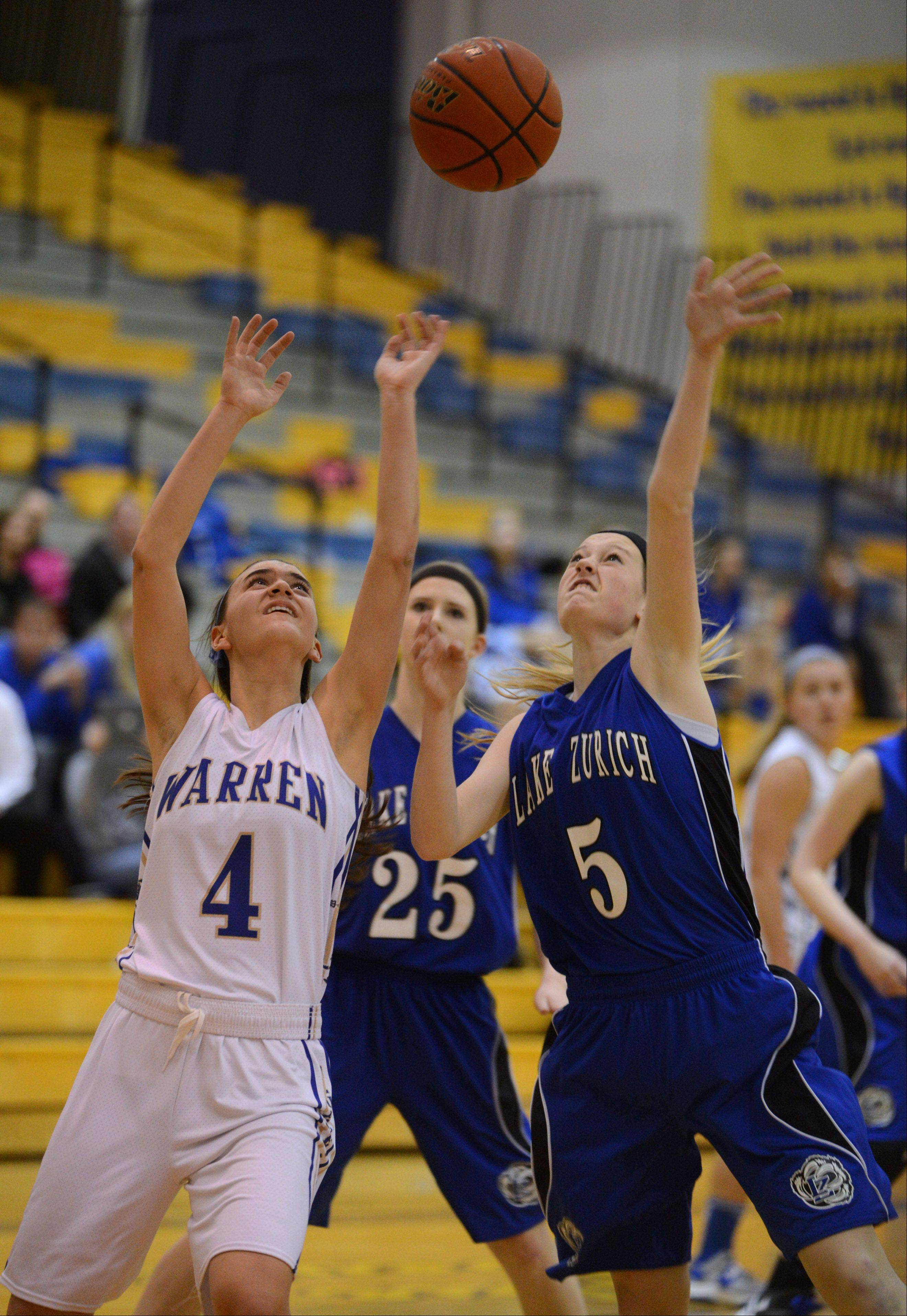 Warren�s Kylie Nedelka (4) and Lake Zurich�s Elly Daleske eye the ball during Monday night�s basketball game in Gurnee.