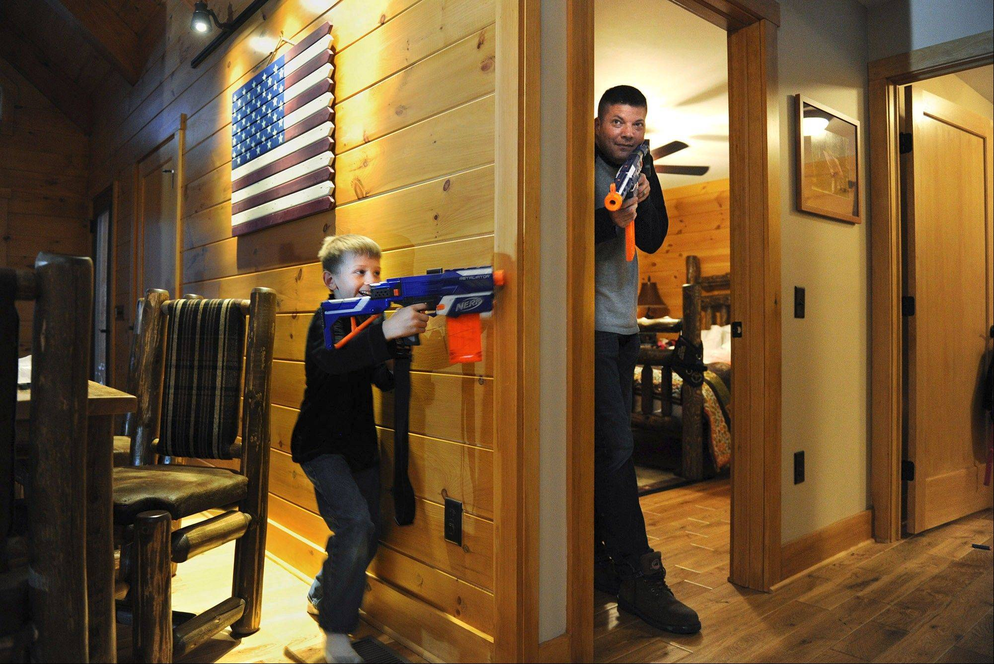 Cole Zajdel, 8, left, hopes to get the drop on his stepfather, Matt Kazee, right, in a Nerf gun game at Boulder Crest Retreat in Bluemont, Va. Kazee is in the Navy; his wife and Cole Zajdel's mother, Liza Kazee, was in the Air Force.