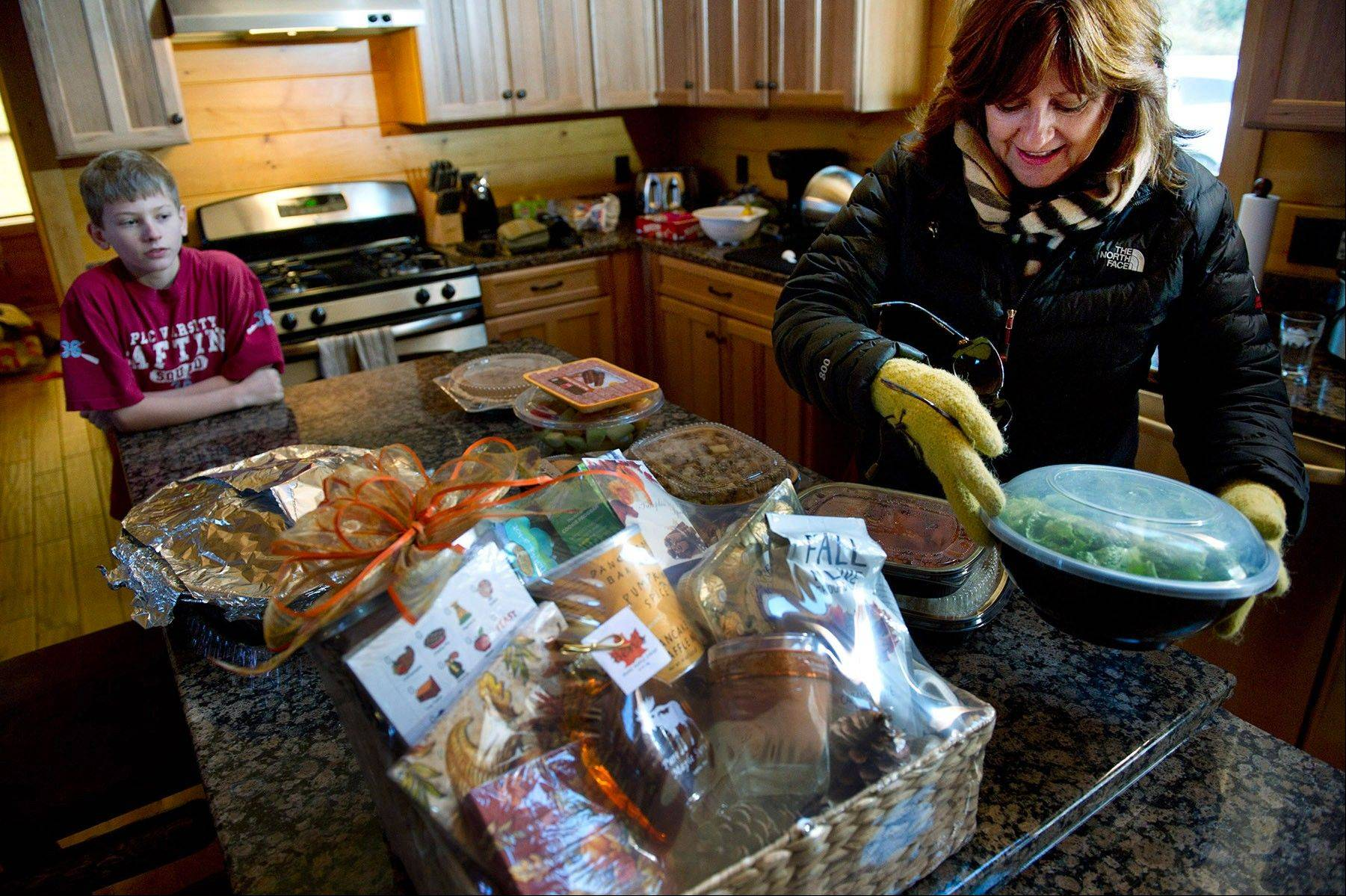 At Boulder Crest Retreat in Bluemont, Va., Julia Falke delivers a Thanksgiving meal to the family of Lucas Zajdel, left, whose mother was in the Air Force and stepfather is in the Navy. The retreat, founded by Falke and her husband Ken Falke, serves wounded military service personnel and veterans.