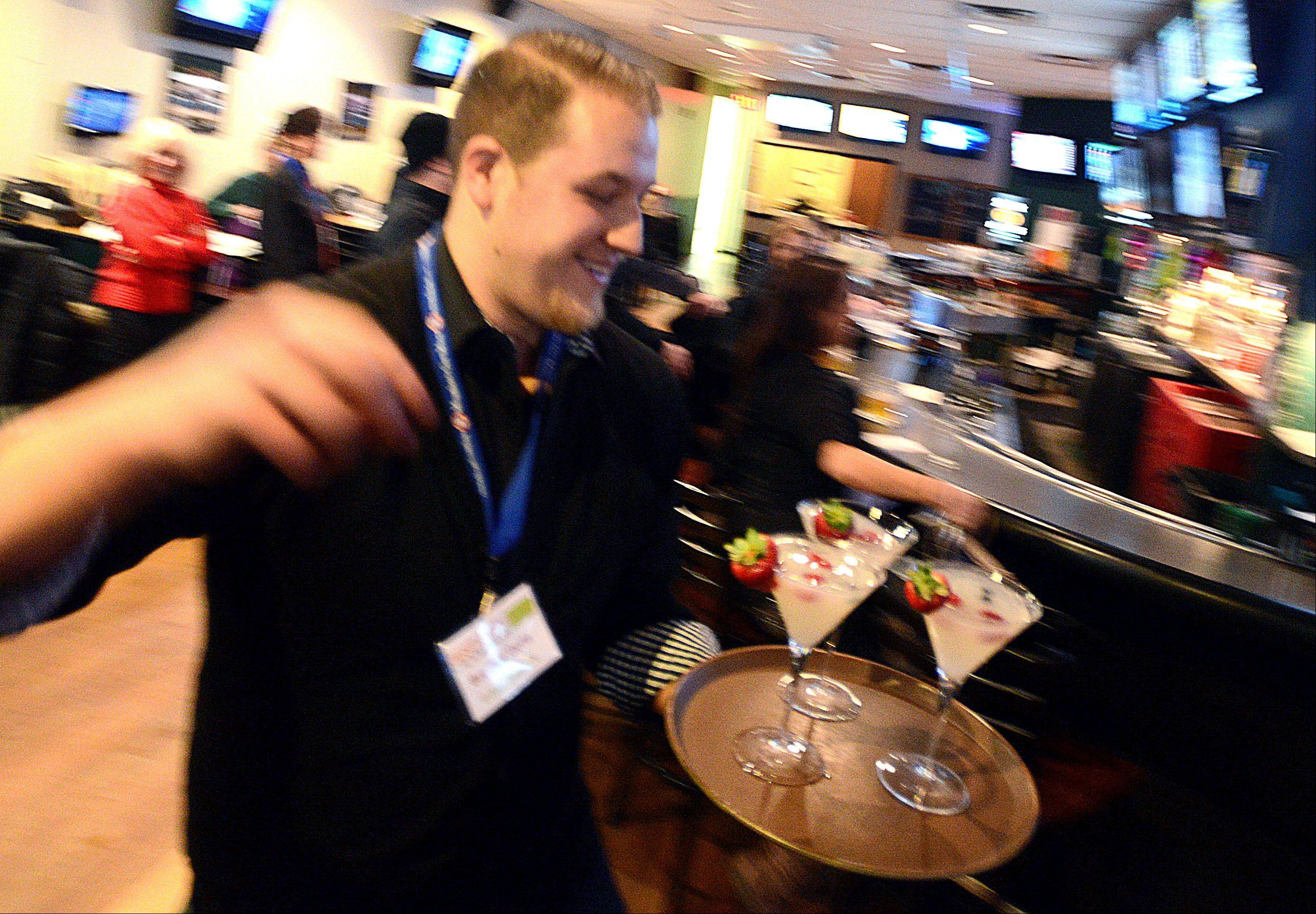 Mixologist Bradley Gertz of Eddie Merlot's Lincolnshire restaurant delivers his Berry White Martinis during the Daily Herald's Best Martini in the 'Burbs Challenge at the At The Post Sports Bar & OTB in Elk Grove Village on Monday night.