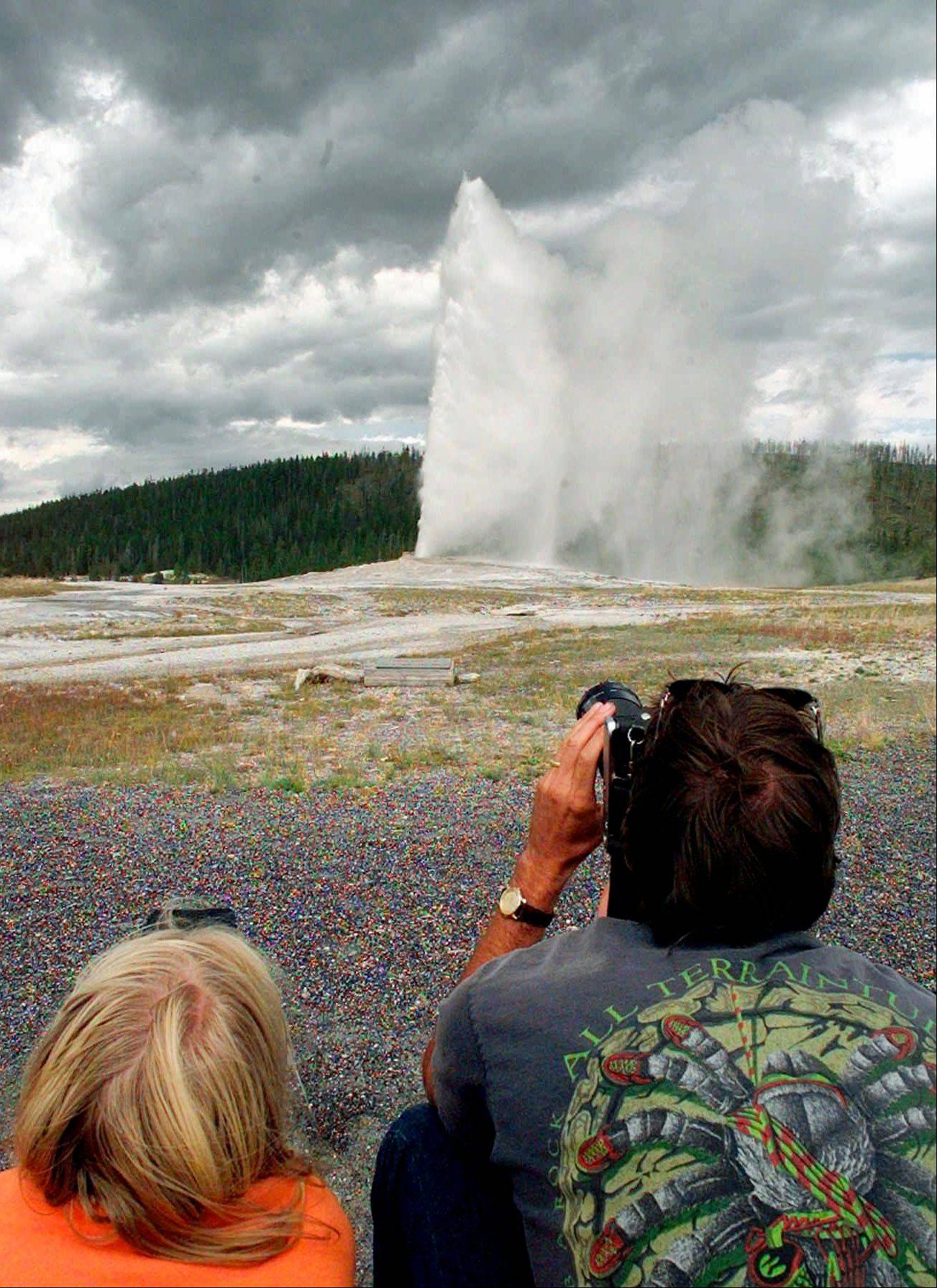 Visitors photograph the Old Faithful geyser at Yellowstone National Park in Wyoming. Hundreds of small earthquakes at Yellowstone National Park in recent weeks have been an unsettling reminder for some people that underneath the park's famous geysers and majestic scenery lurks one of the world's biggest volcanoes.