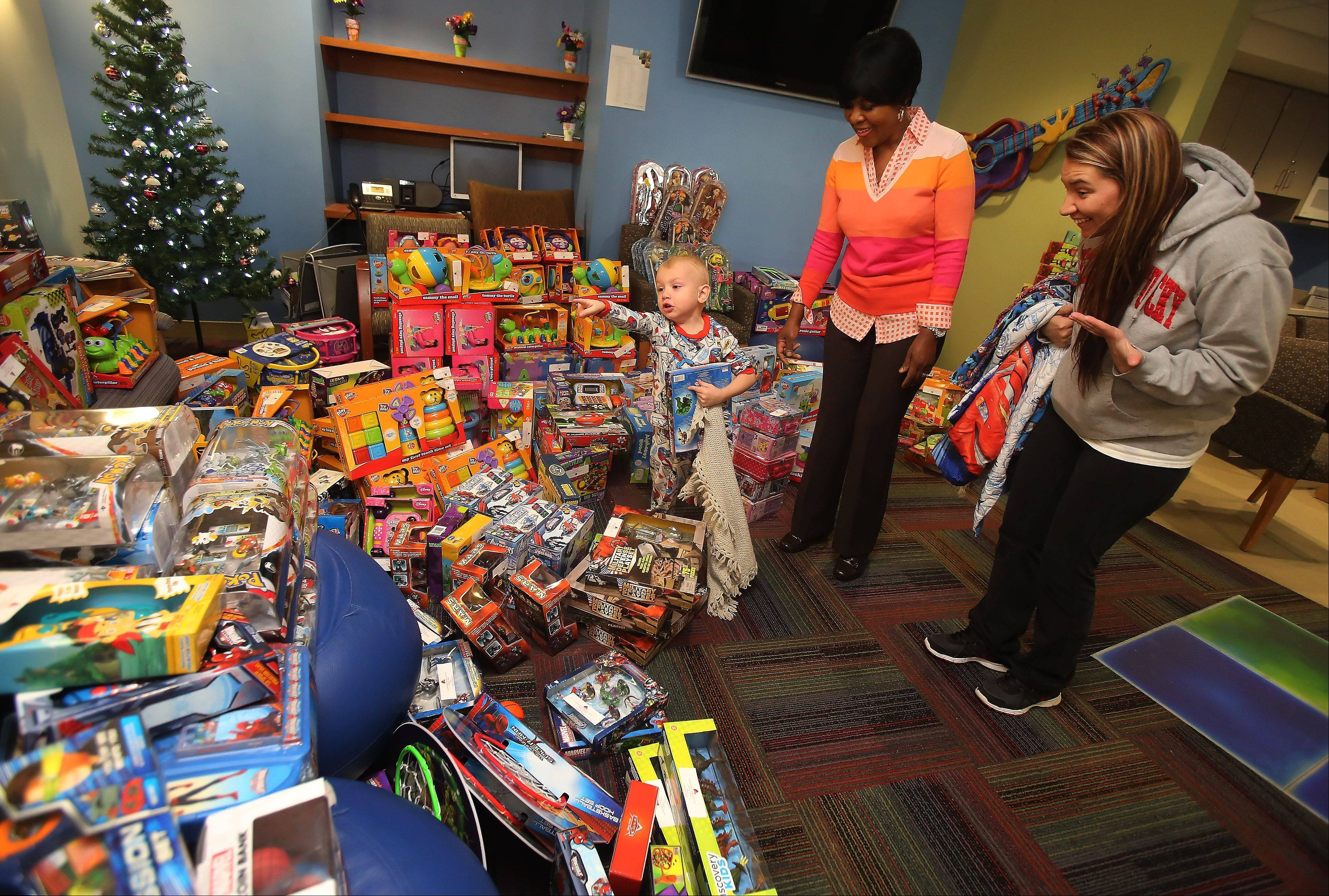 Brandon Hinojosa, 2, of Lake Zurich, and his mother Brandy, right, look for a gift Monday among the hundreds purchased by Advocate hospital cafeteria worker Jessie Tendayi. This is the fourth year Tendayi has purchased gifts for pediatric patients. She gave out hundreds Monday to children at Advocate Children's Hospital in Park Ridge.