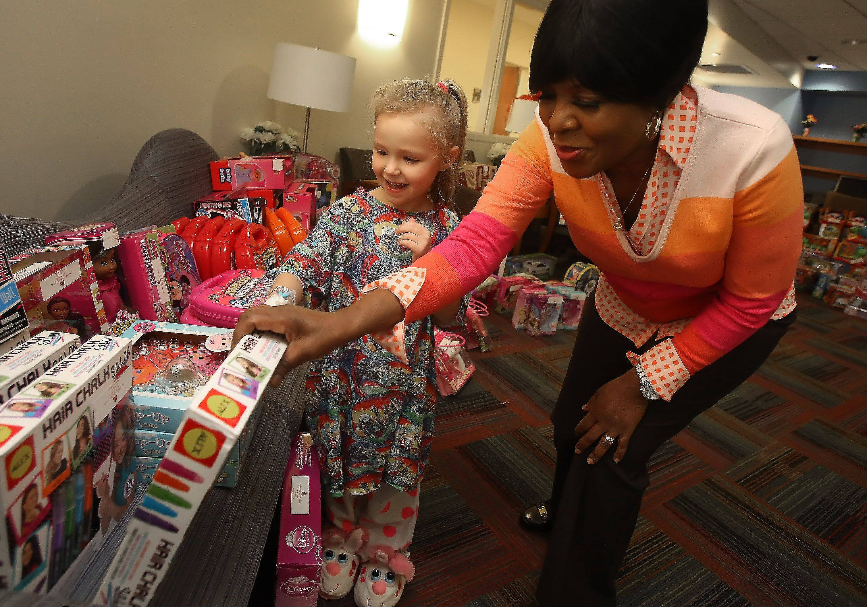 Nicole Ciechanowski, 5, of Morton Grove picks a toy Monday with help from Advocate hospital cafeteria worker Jessie Tendayi at Advocate Children's Hospital in Park Ridge. Tendayi spent $2,200 of her own money to buy about 700 gifts for pediatric patients at Advocate children's hospitals in Park Ridge and Oak Lawn.