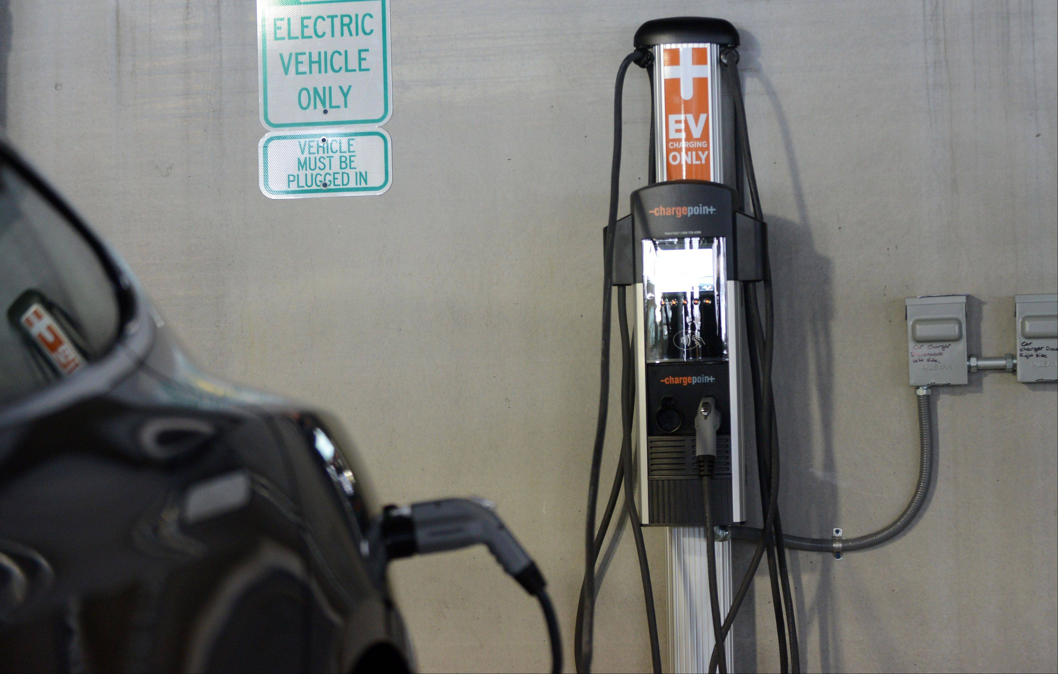 A car is plugged into the first car charging station offered by the city of St. Charles Monday at the First Street garage.