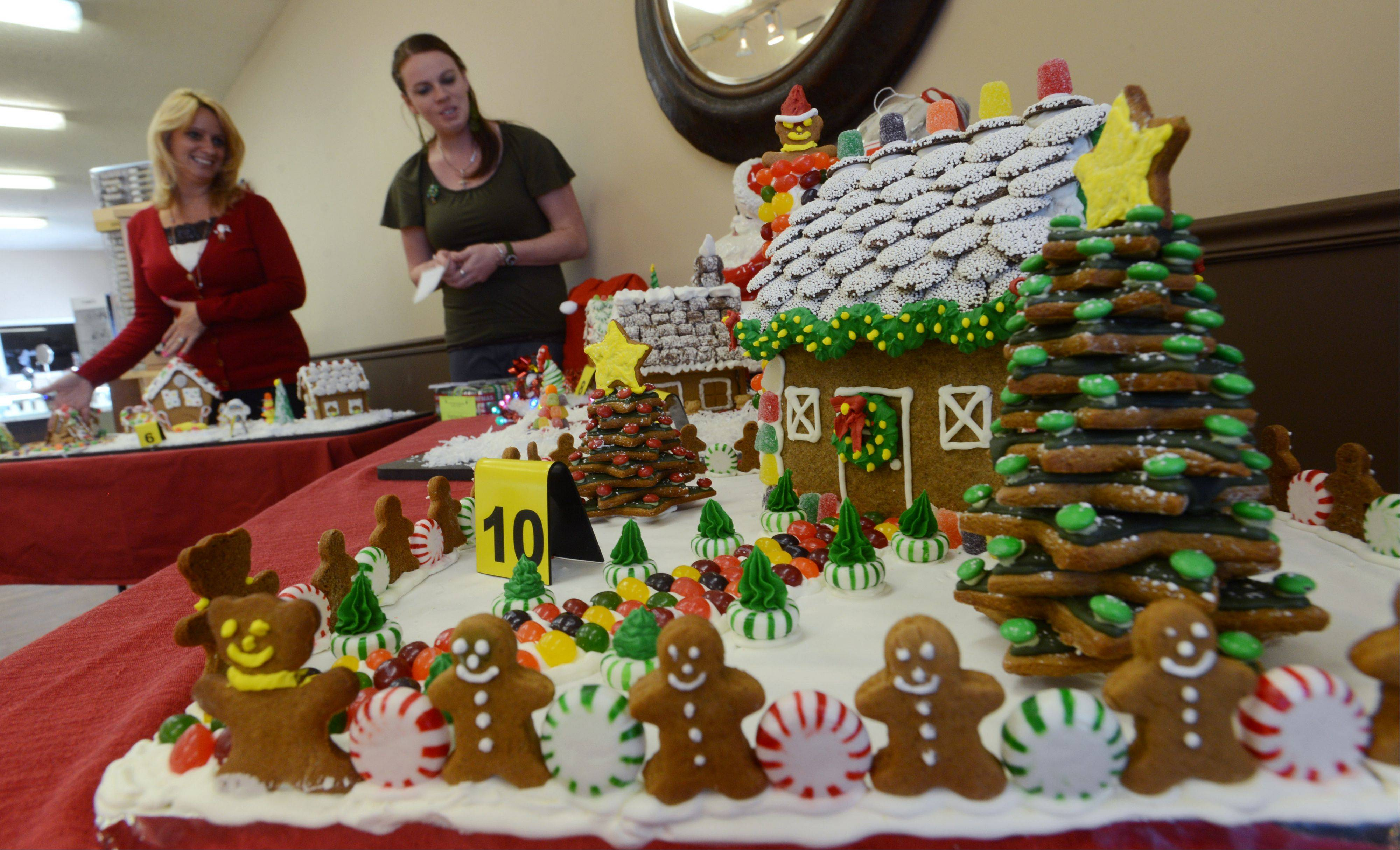 Ruth Hogan, left, and her daughter, Renee Evans, co-owners of Paradise Jewelry & Treasures in Fox Lake, look over the six gingerbread houses on display in their store. Monday was the final day to vote for the 7th annual Fox Lake Area Chamber of Commerce & Industry gingerbread house contest.