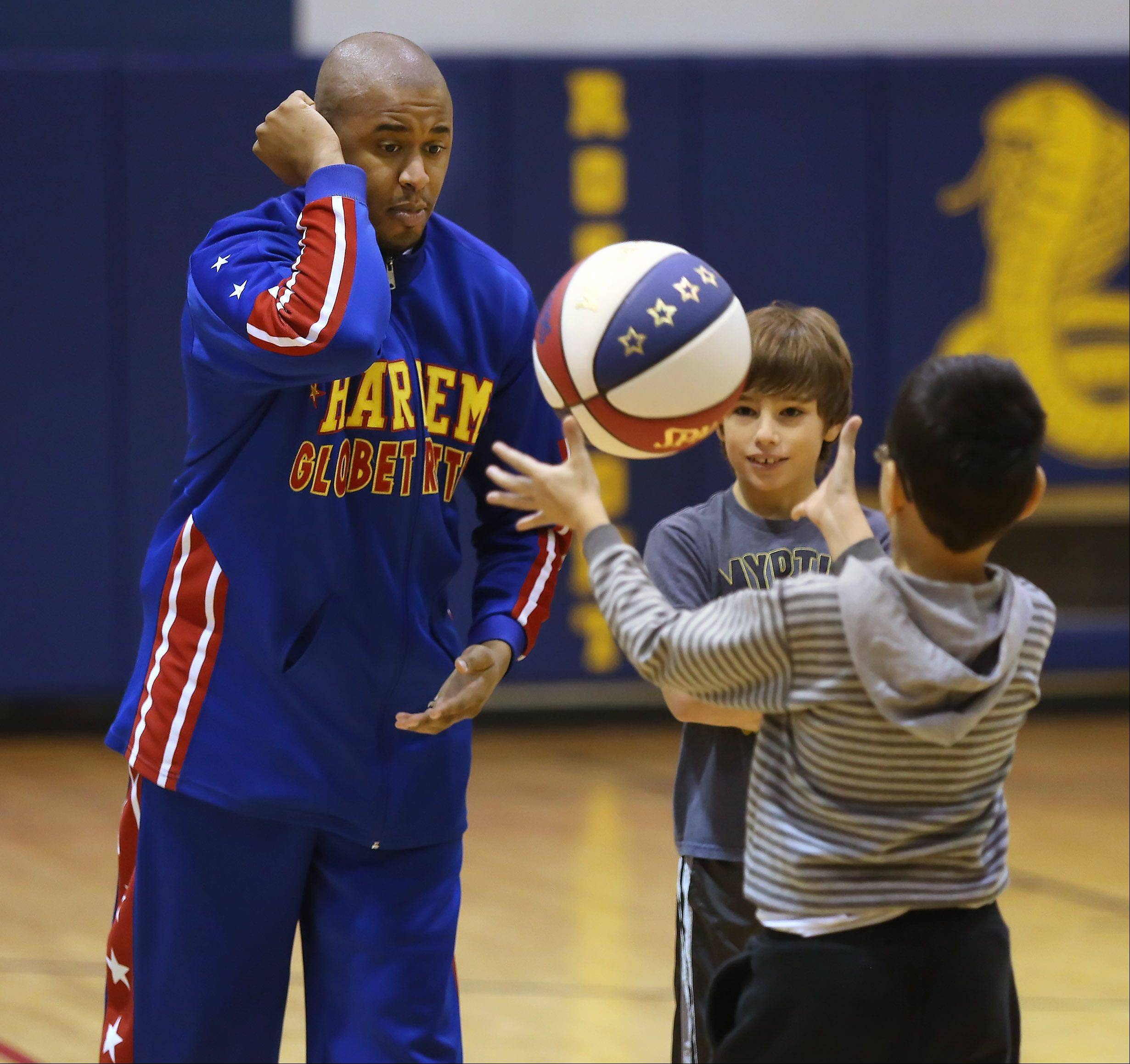 "Harlem Globetrotter Shane ""Scooter"" Christensen teaches a trick to Rosemont Elementary School fifth grader Landon Kruppa and second grader Bobi Duler during an appearance at the school Monday morning. Christensen and fellow Globetrotter Alex ""Moose"" Weeks also taught students about bullying and tools they can use to prevent it."