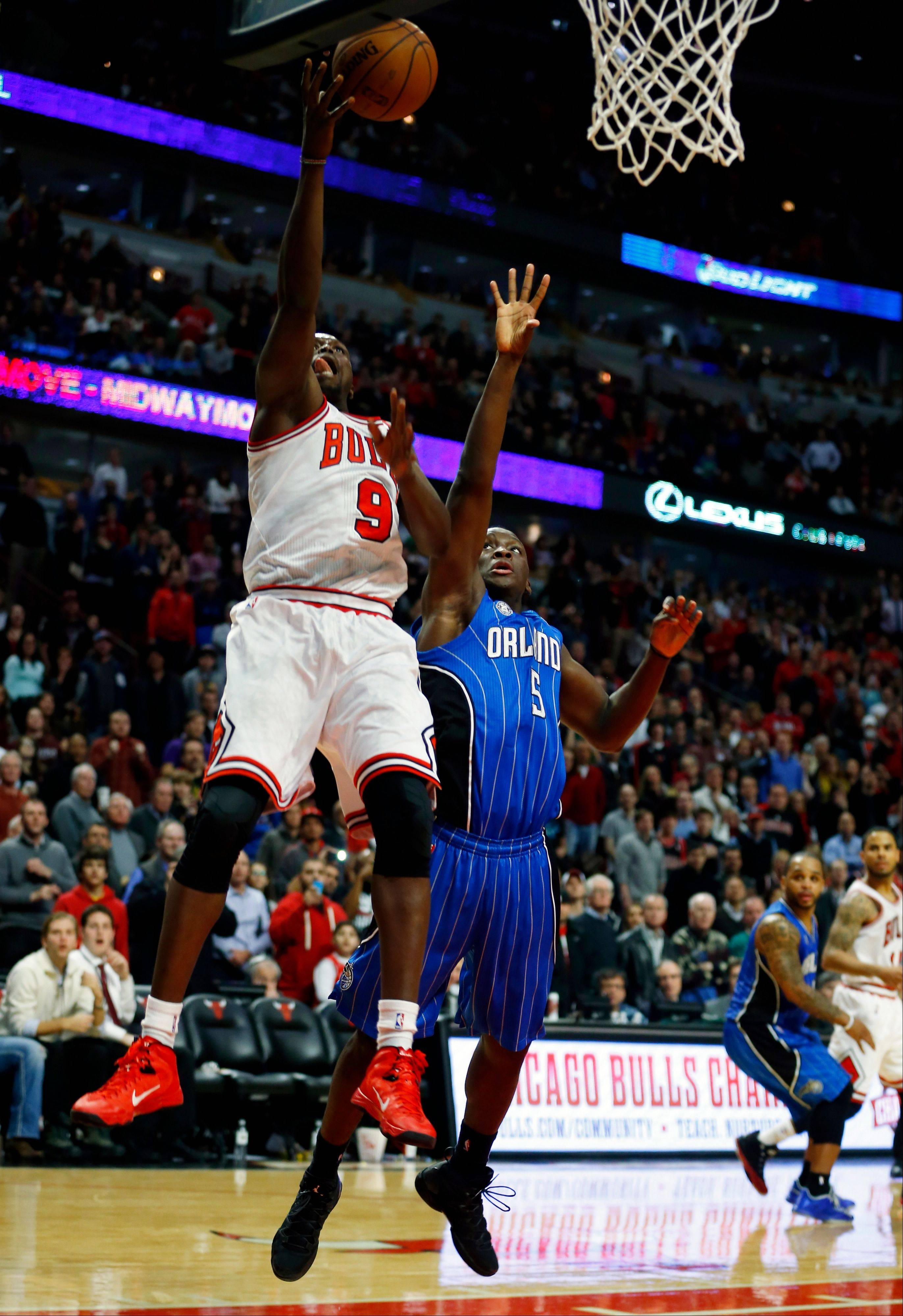 The Bulls' Luol Deng gets past Magic guard Victor Oladipo as he goes in for a layup during the second half Monday night at the United Center.
