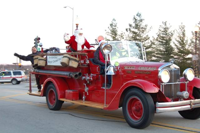 West Chicago Mayor Ruben Pineda waived to passersby as Lieutenant Mike Buenrostro, Jr. and Melissa Medeiros delivered Santa Claus to Frosty Fest aboard The General, the West Chicago Fire Protection District's antique fire engine.