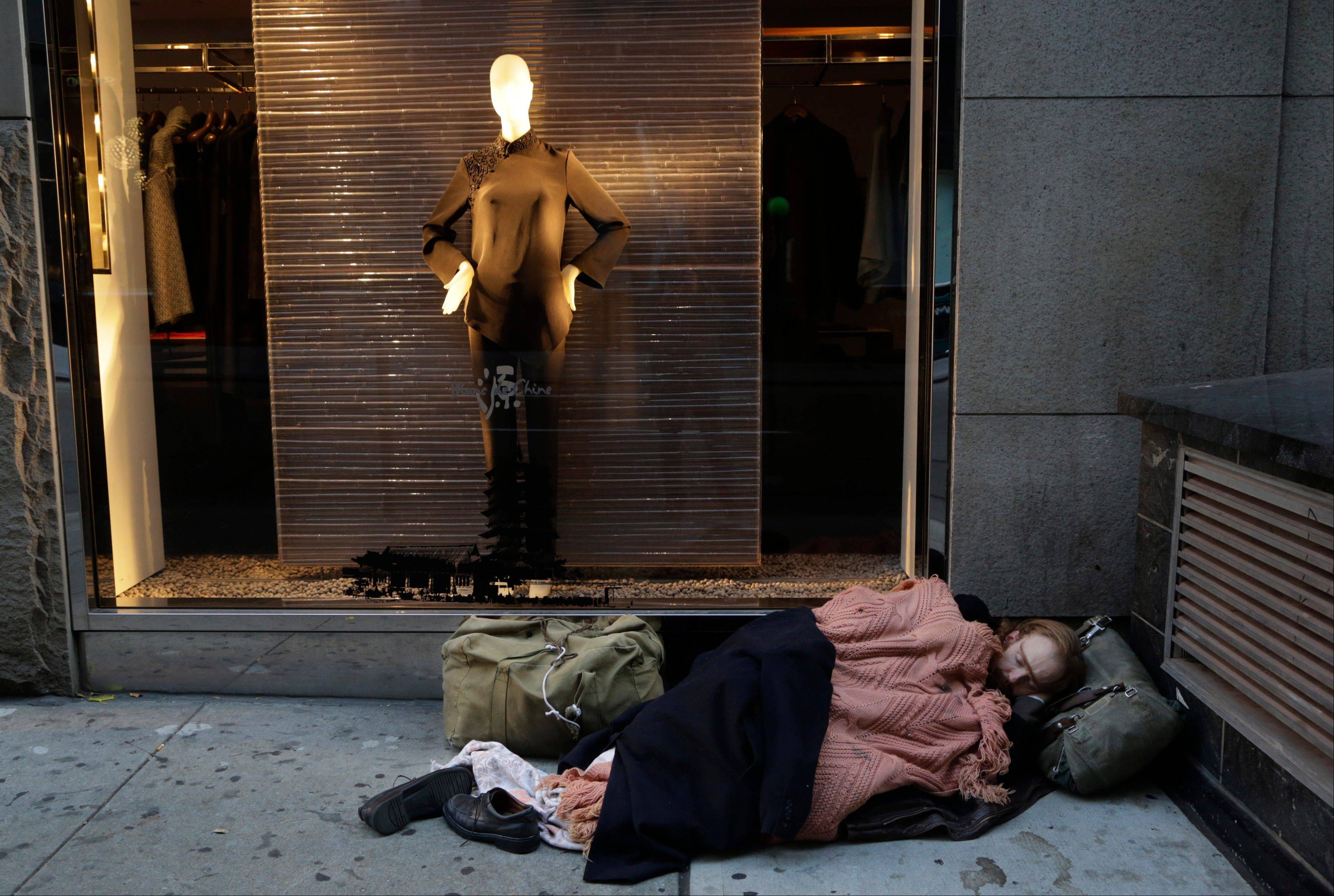 A destitute man sleeps on the sidewalk under a holiday window at Blanc de Chine in New York. The growing gap between the richest Americans and everyone else isn�t bad just for individuals it�s hurting the U.S. economy says a majority of more than three dozen economists surveyed in December 2013 by The Associated Press.