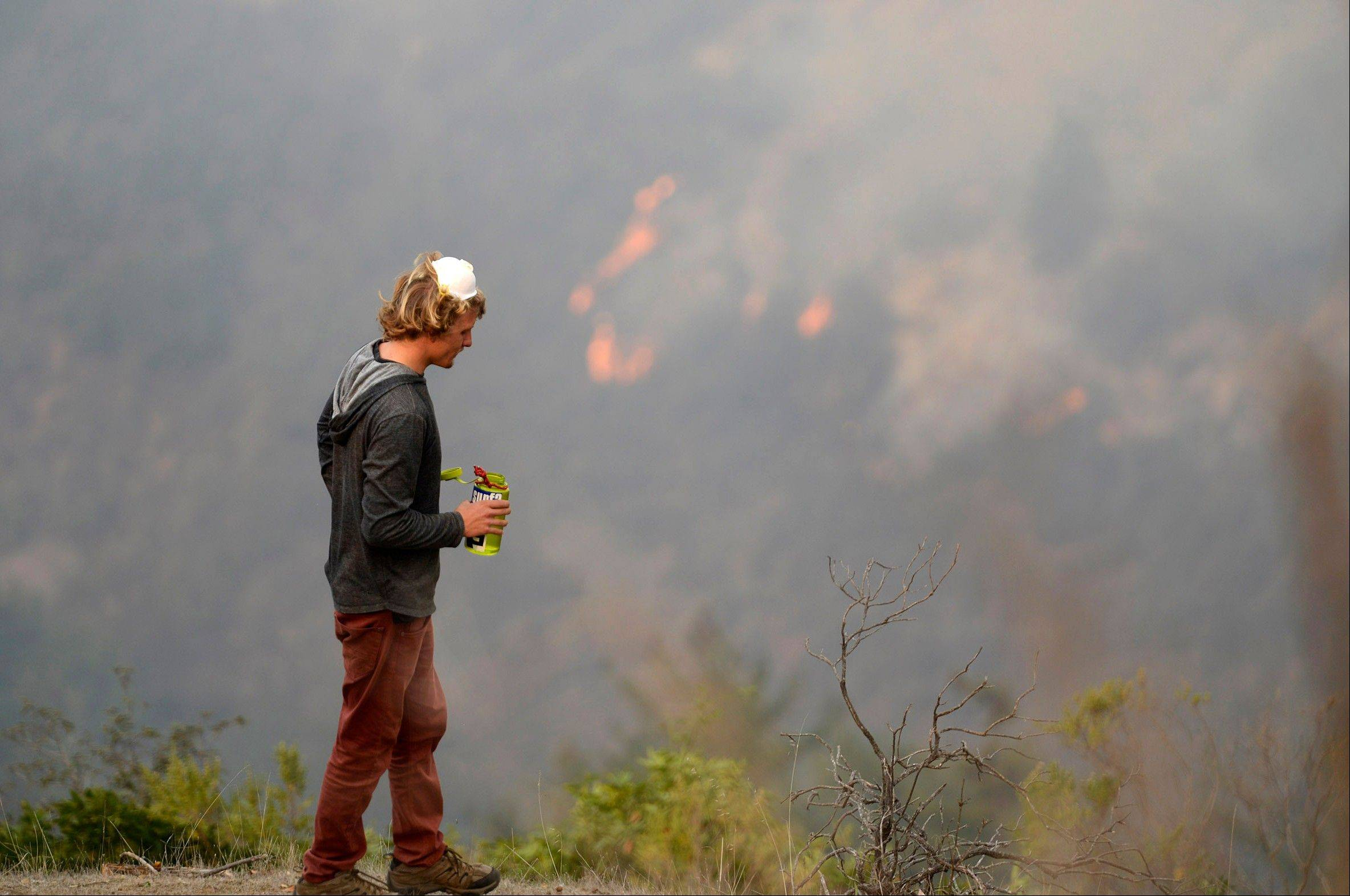 Garritt Cooper, 25, of Idaho takes a water break while clearing a fire break near a friend�s home as firefighters battle a fire across the ridge in Big Sur, Calif., Tuesday.