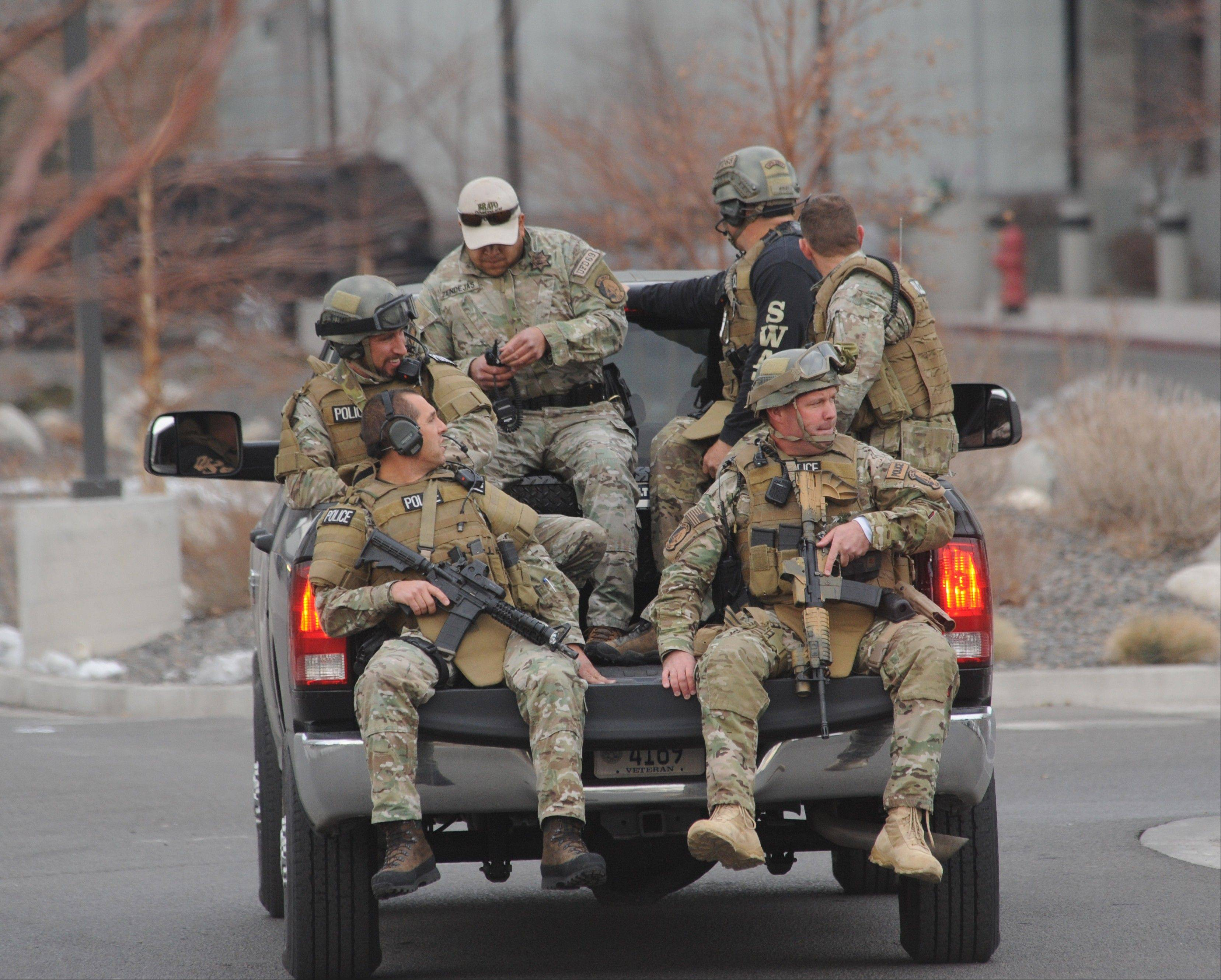 SWAT team members are trucked from near the Renown helicopter pad to the Renown Medical Center where a lone gunman killed one person and critically wounding two others before killing himself at the sprawling medical campus Tuesday in Reno, Nev.