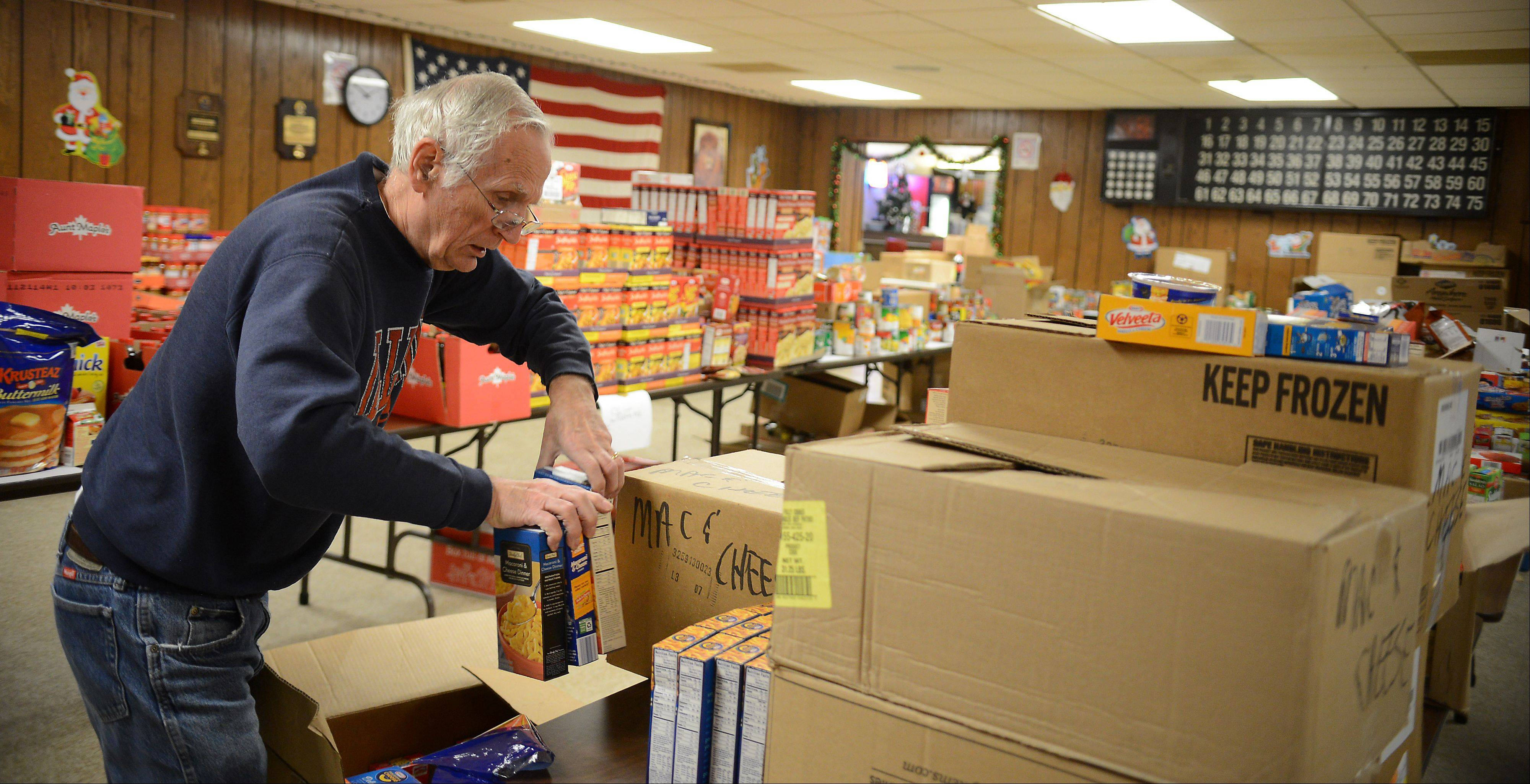 Allan Shelton of the South Elgin Lions Club unpacks boxes of donations and sorts food Tuesday that will be distributed to around 200 needy families in the area this week. They also have coats and toys for those in need.