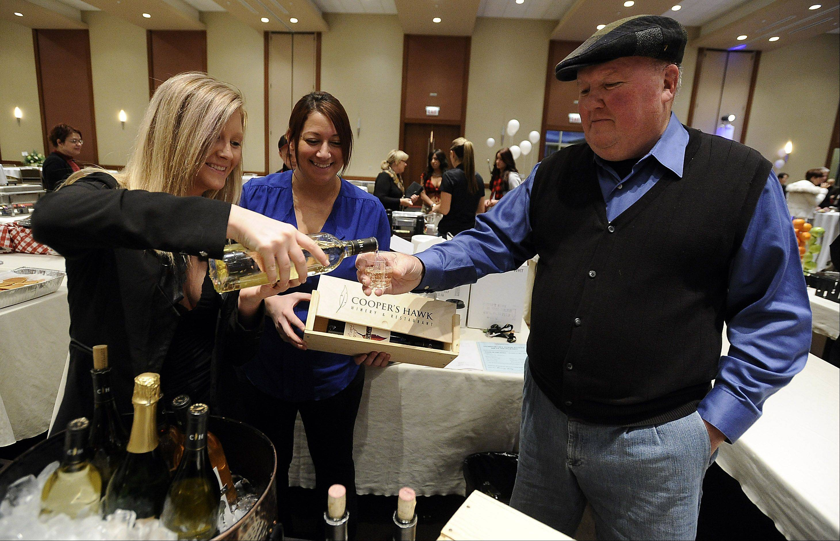 Kristy Framke, assistant event coordinator for Cooper�s Hawk of Wheeling, pours Dennis Degelmann of Arlington Heights a drink. Kelly Bulmash, also of Cooper�s Hawk, looks on.