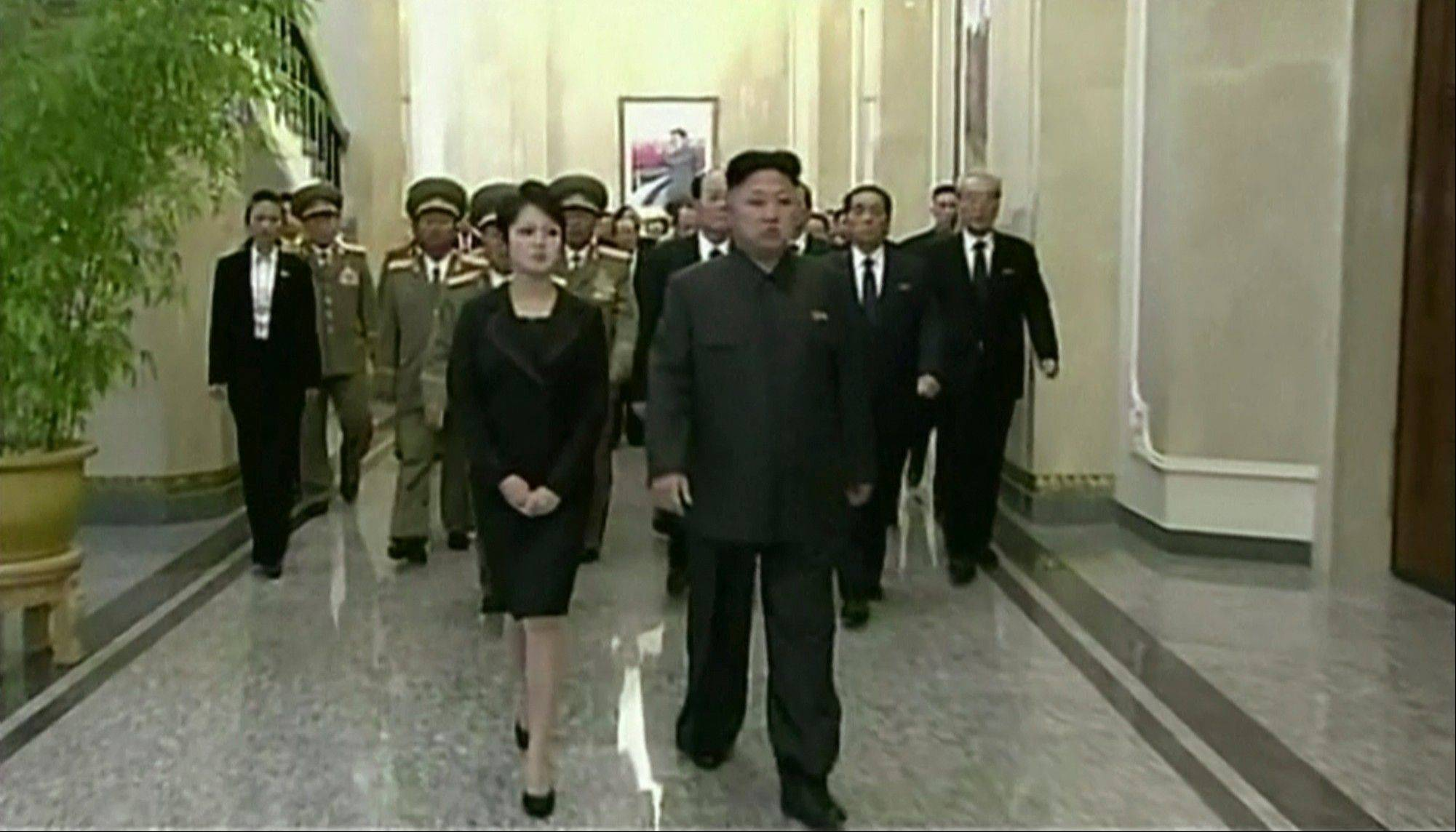 North Korean leader Kim Jong Un, center right, his wife, Ri Sol Ju, and high ranking officials walk as they visit the Kumsusan Palace of the Sun on the second anniversary of the death of his father, former leader Kim Jong Il.