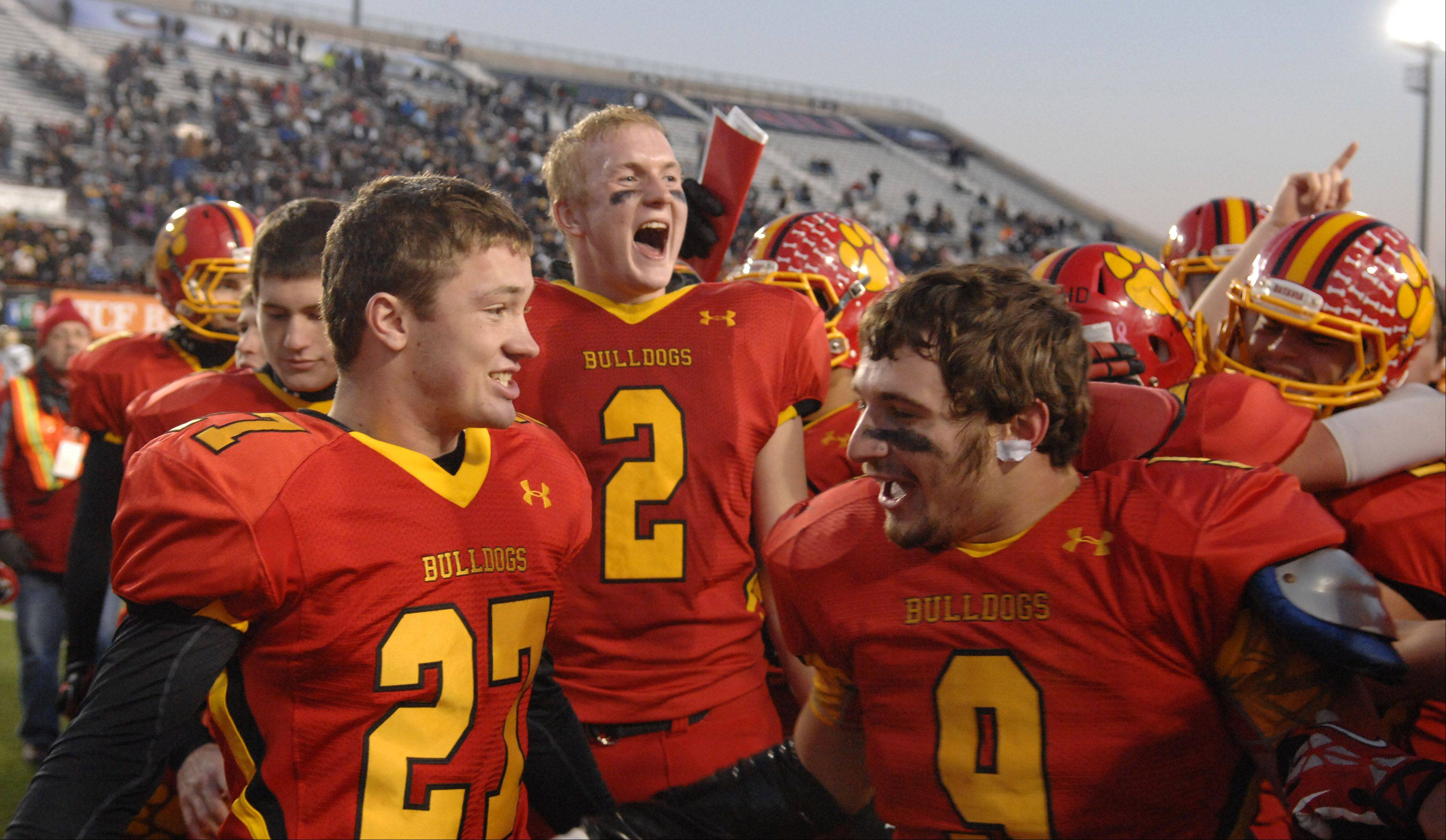 With their fans cheering in the background, Batavia players celebrate their Class 6A football championship at Huskie Stadium in DeKalb on Nov. 30