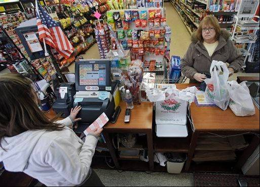 Janet Humpal, right, buys Mega Millions lottery tickets from cashier Brittany Beardon at the Bi Rite market in Olmsted Township, Ohio.